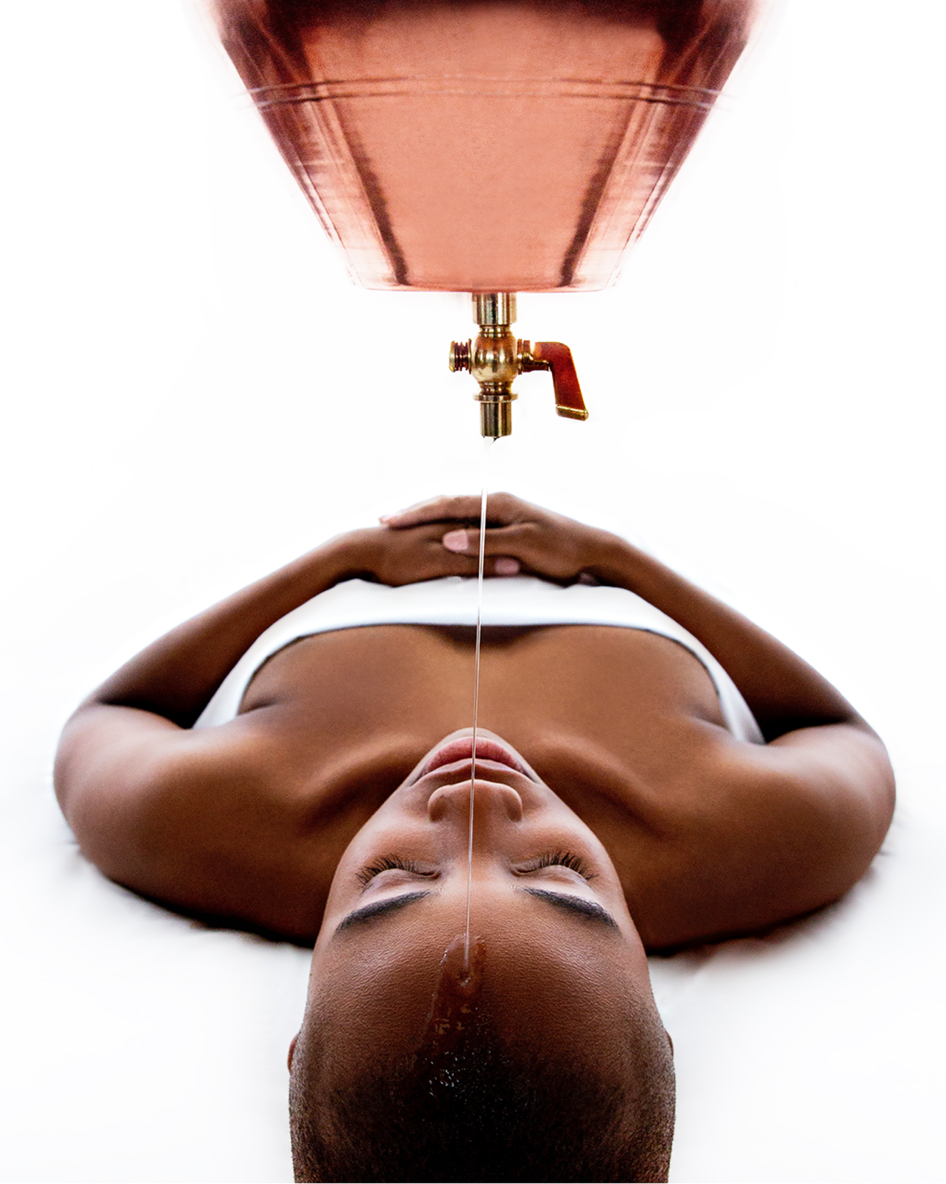a woman laying down on her back facing toward a nozzle that is slowly dripping oil on her forehead. She is wrapped in a white towel.