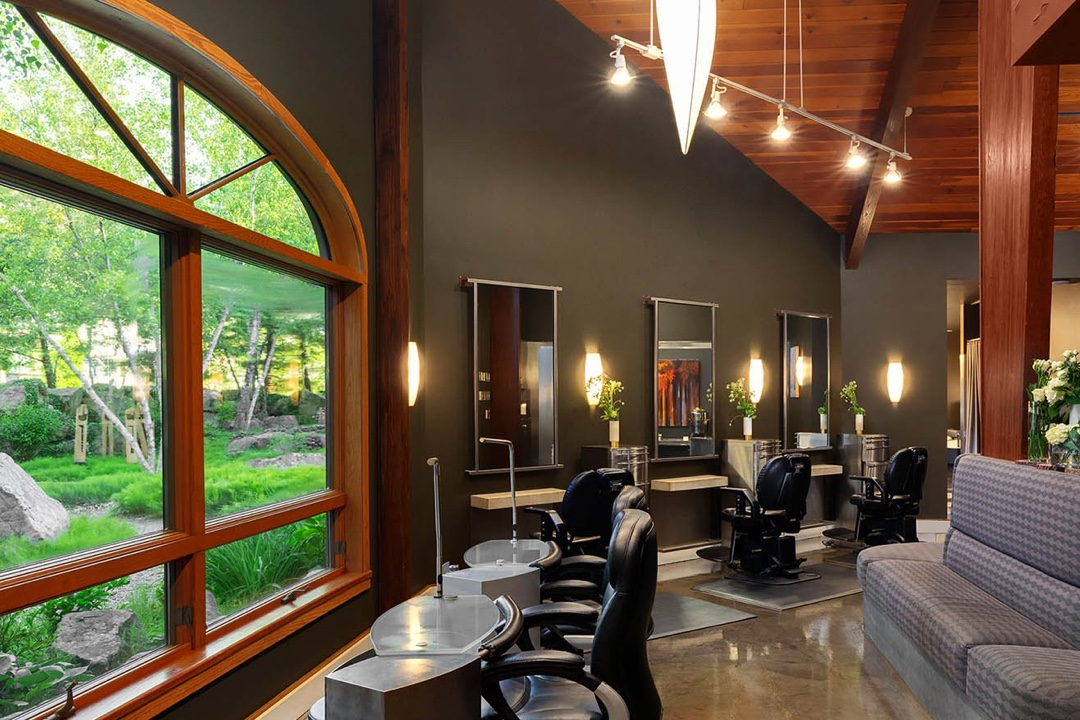 the interior shot of a beauty salon. there are plush black leather chairs in front of mirrors and nail painting tables. There are windows with a view of nature