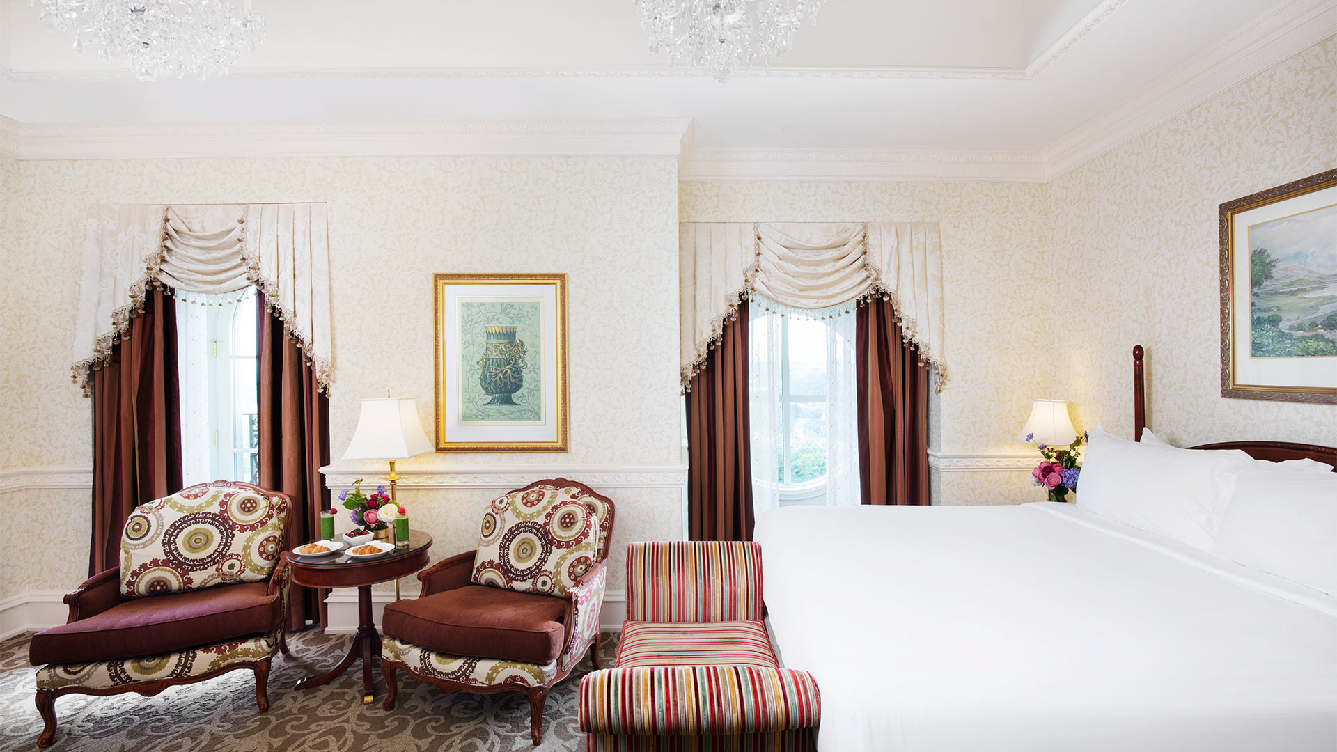 interior shot of The Chateau's Club King accommodation. White linen king bed, a sitting area and windows overlooking the grounds.