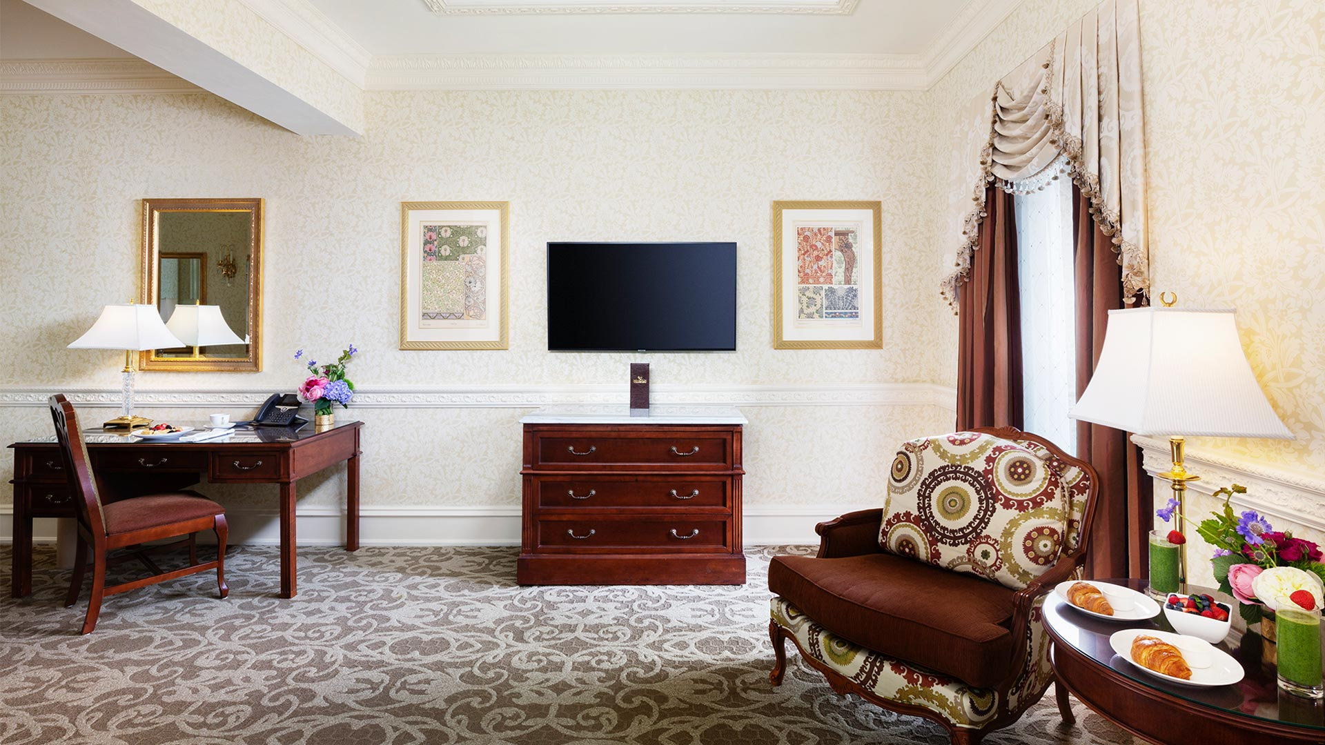 sitting area with a desk, tv, dresser and chairs. there is breakfast on the side table between the two chairs
