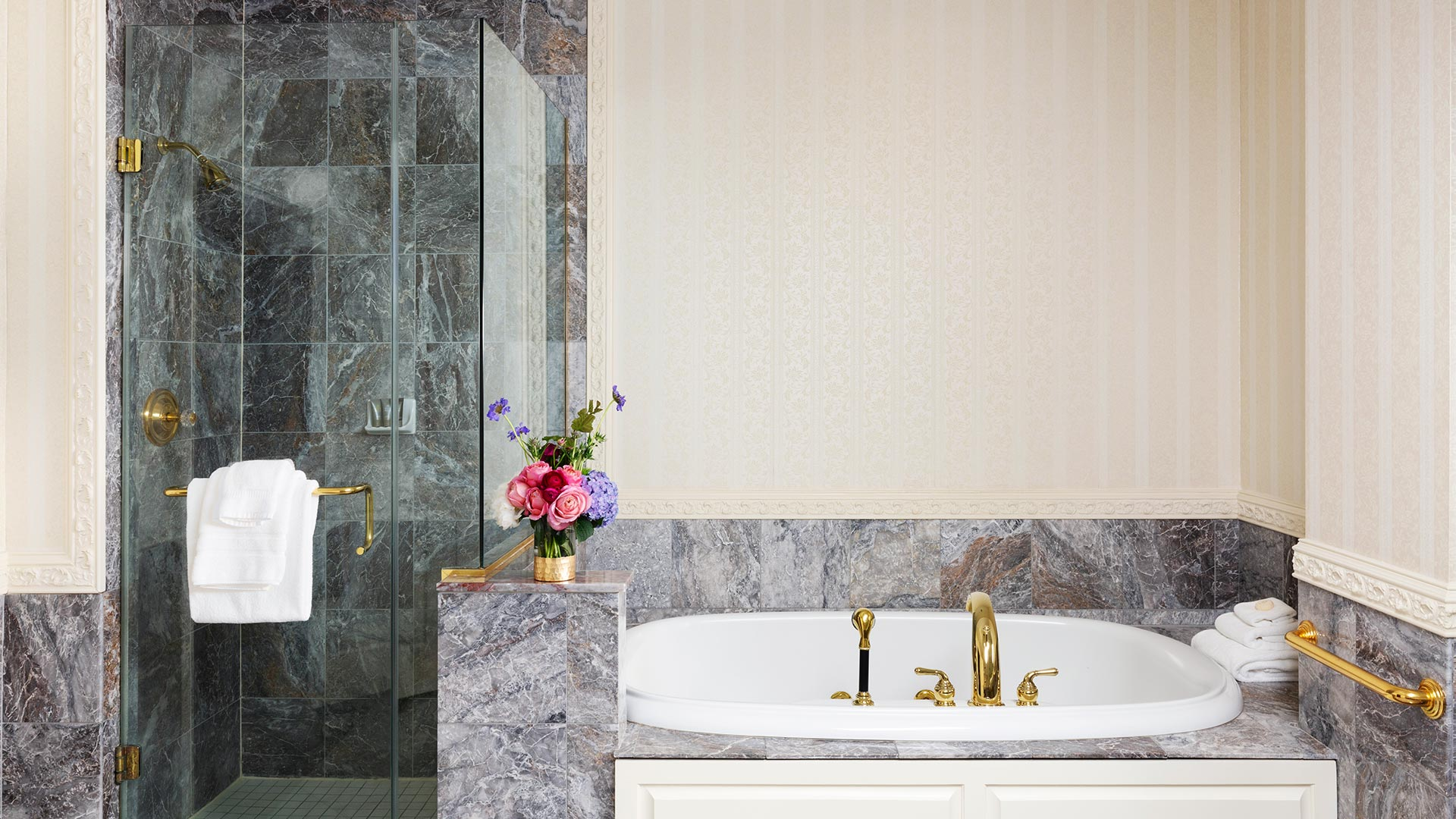 serene bathroom interior. neutral colored walls and tiles. There is a walk-in shower and whirlpool bathtub pictured