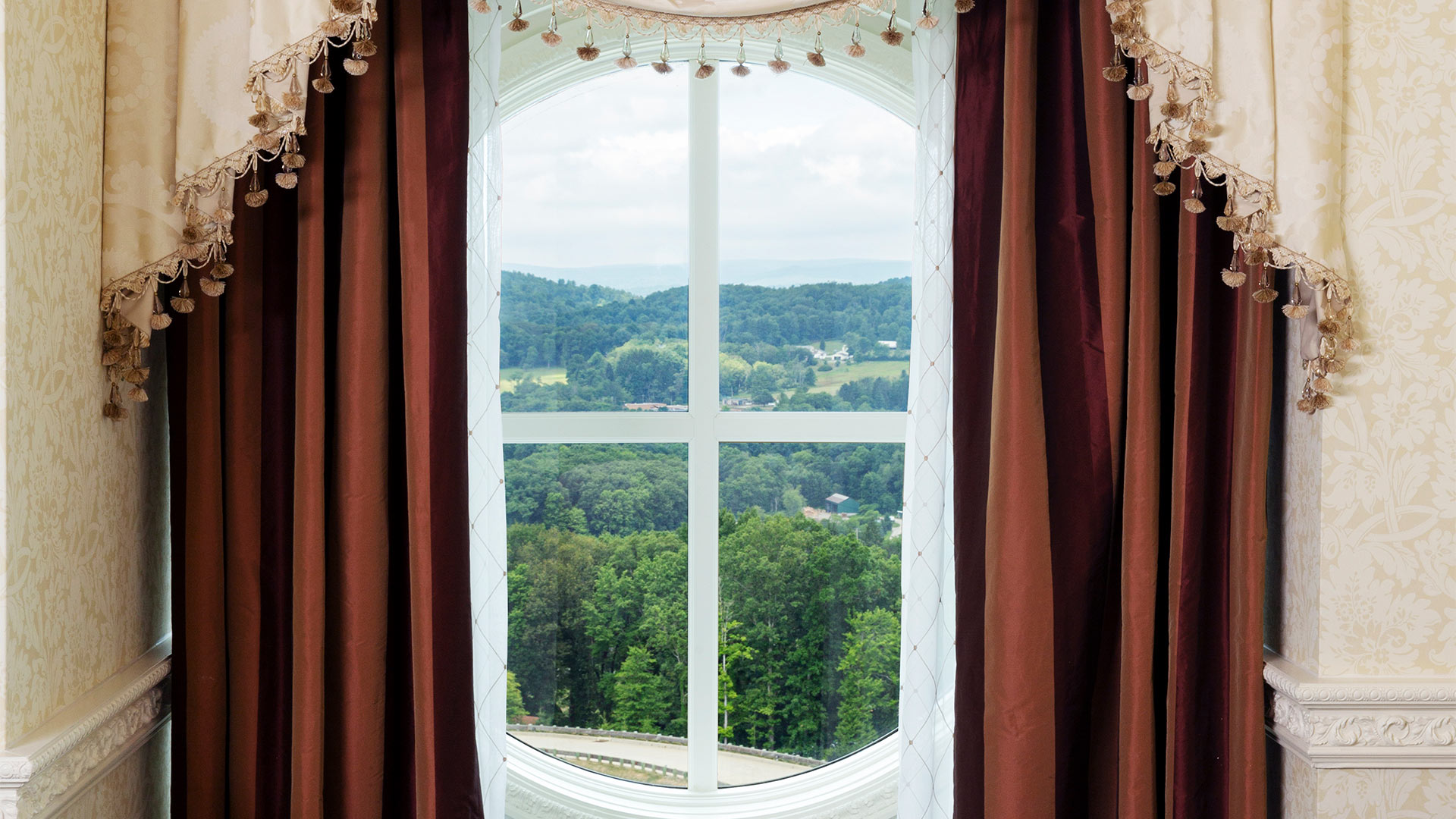 large window overlooking the resort grounds. beautiful red and white curtains frame the window
