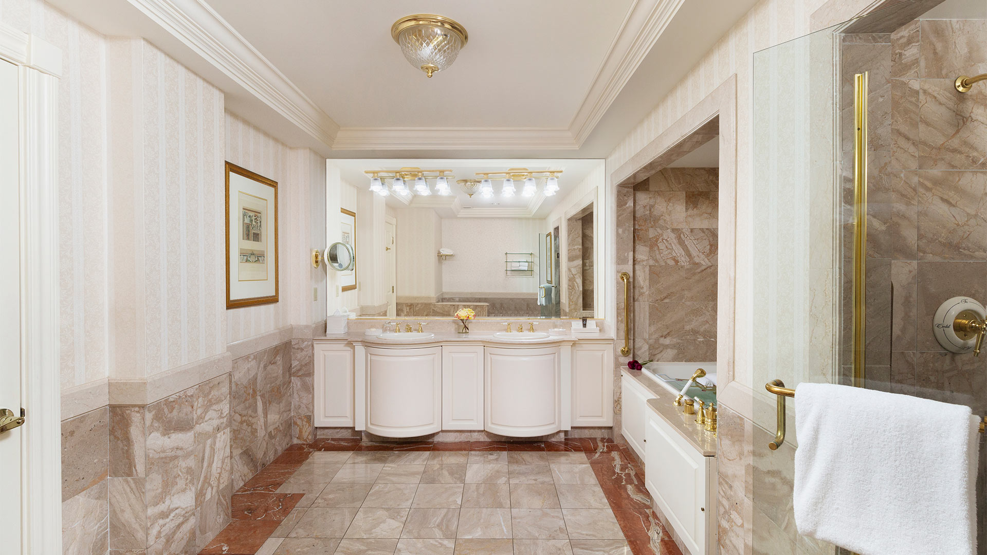 interior shot of a bathroom. the colors are a neutral beige. There is an elegant double sink with a large mirror and a shower and bath combination to the right of the sinks.