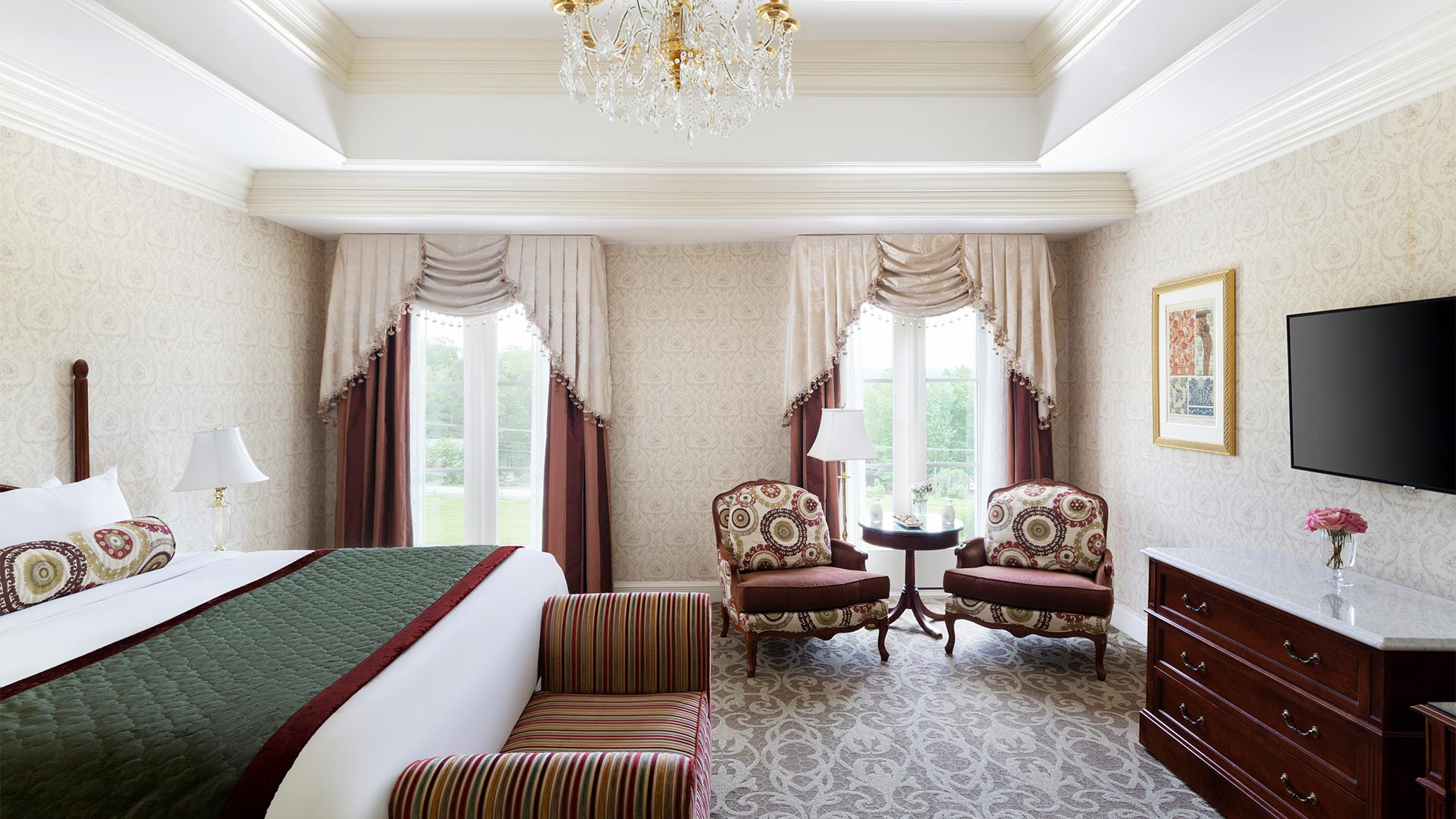 interior shot of The Chateau's king accommodation. There is a king bed with white and green linens. The room also includes views of the resort grounds, a small sitting area and a tv with a dresser.