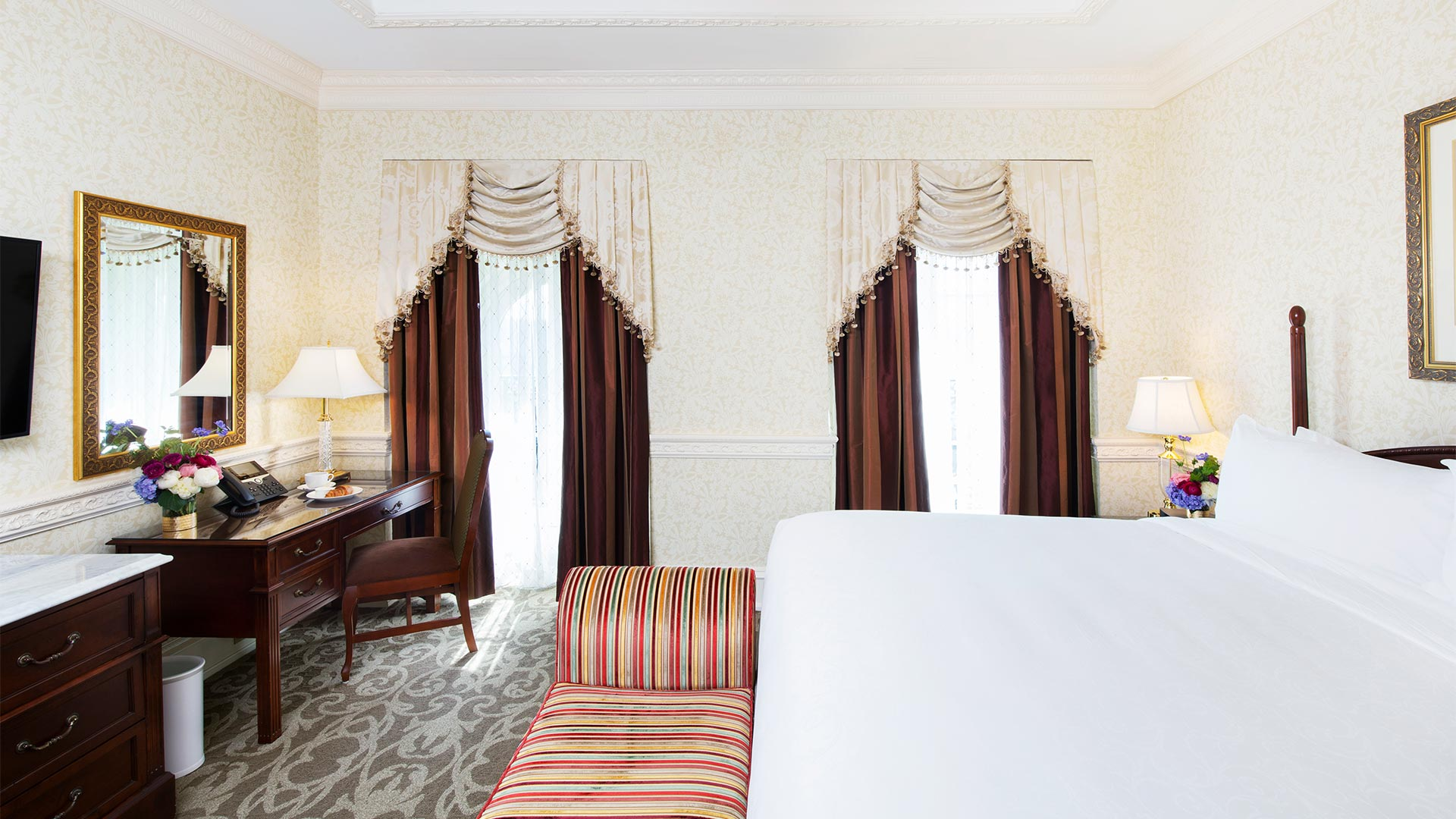 interior shot of the bedroom area. There is a king bed with a desk, TV and sitting bench at the foot of the bed. Two windows give views of the resort.