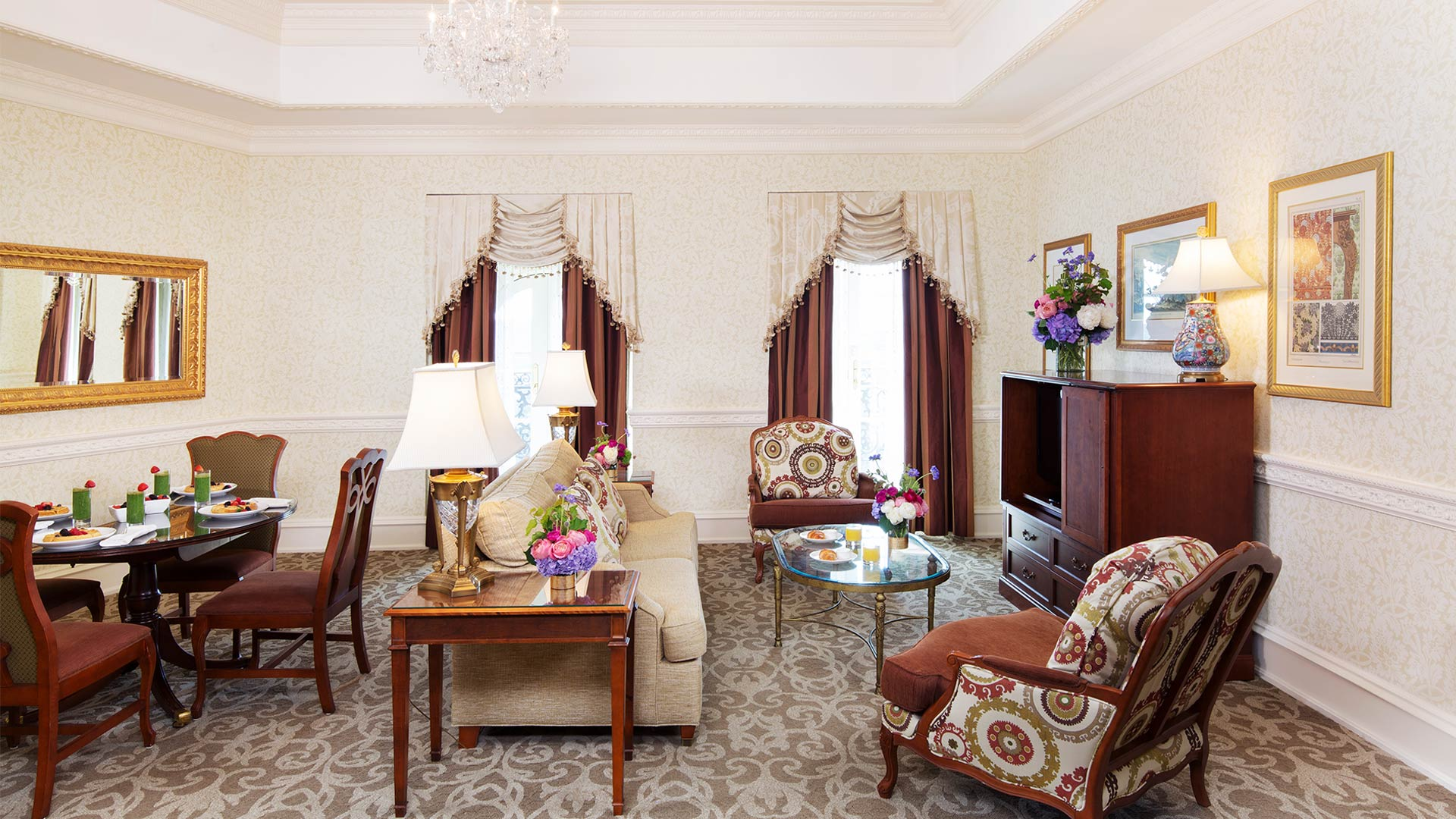 interior shot of The Chateau's club suite's sitting area. There is a plush couch, two chars and a dining room table. There is also a TV and two windows with views of the resort.