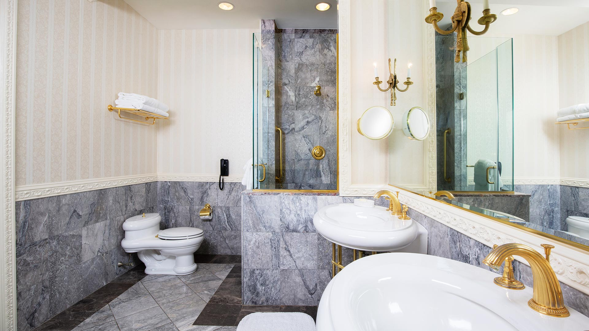 interior of the suite's bathroom. the room has neutral gray tiling, two sinks, a large mirror, and a walk in shower.