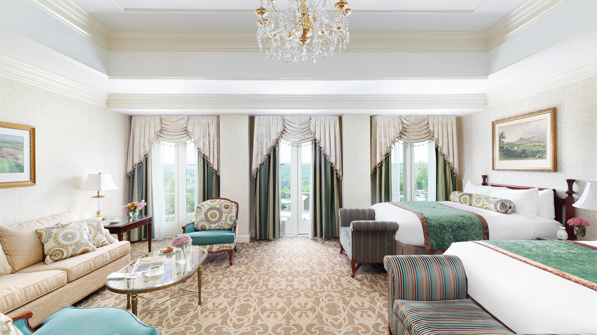 interior shot of The Chateau's junior double room. There are two queen beds with green and white linens and sitting benches at the foot of each. There are three windows overlooking the resort grounds and a sitting area