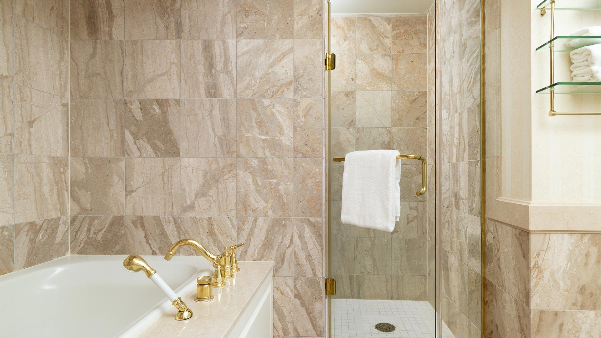 detail shot of the bathroom. The tiling is a neutral beige and the whirlpool bathtub is white with gold hardware. There is also a small shower next to the bathtub.