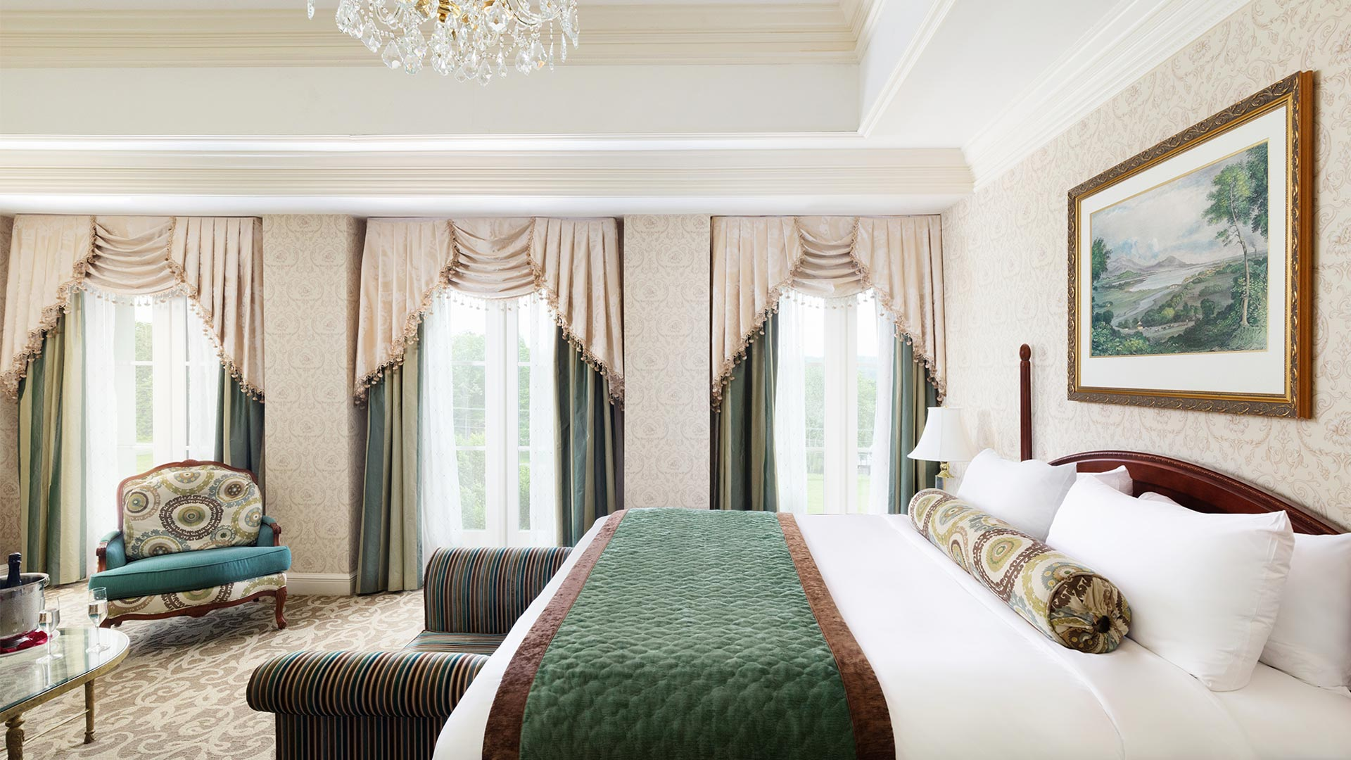 interior shot of The Chateau's Junior King Suite bedroom. There is a king bed with green and white linens with a sitting bench on the end of the bed. There is a sitting area and three large windows overlooking the resort grounds.