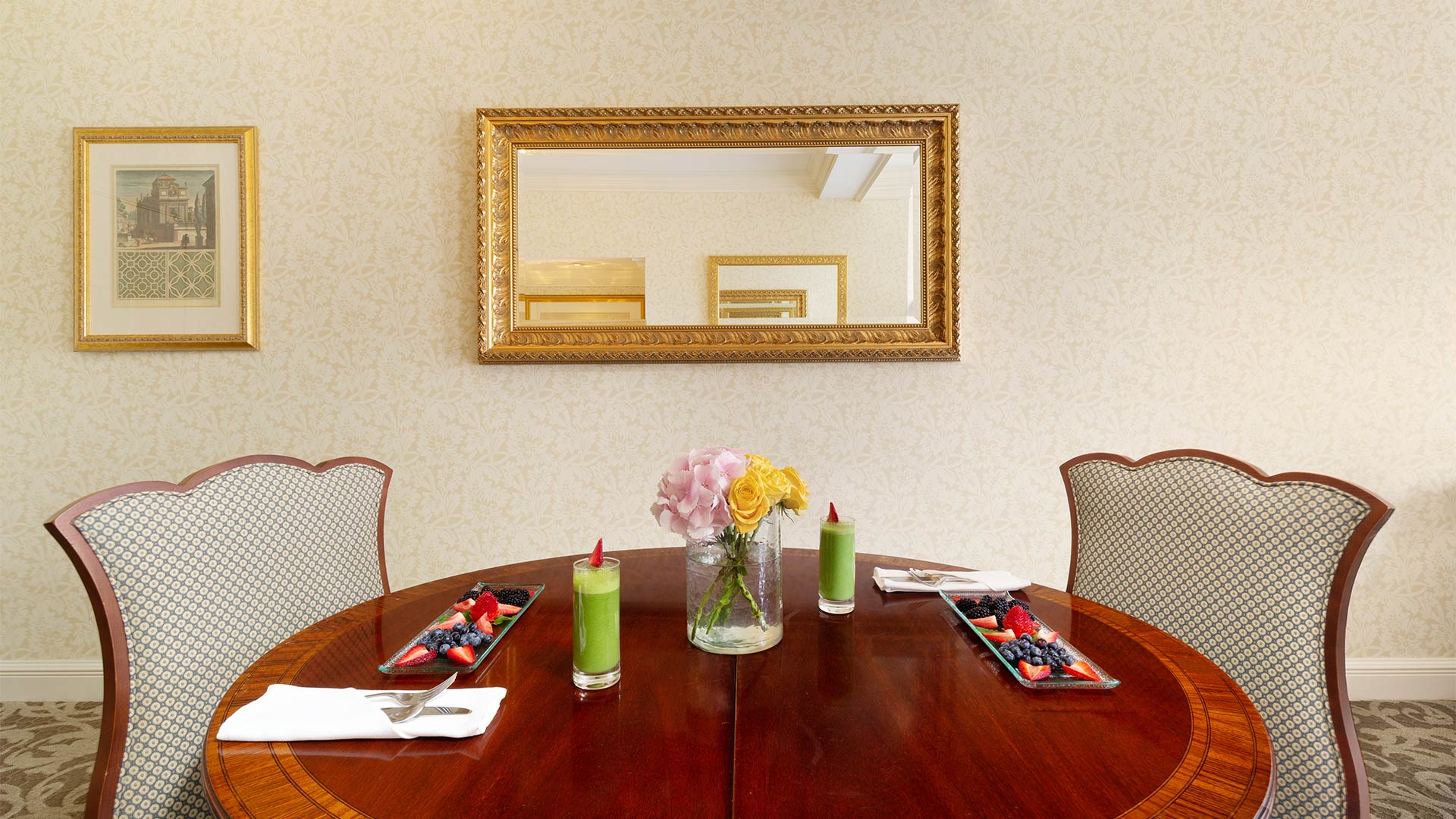 detail shot of the suite's dining area. Two chairs are placed around a circular table. There is breakfast on top of the table.