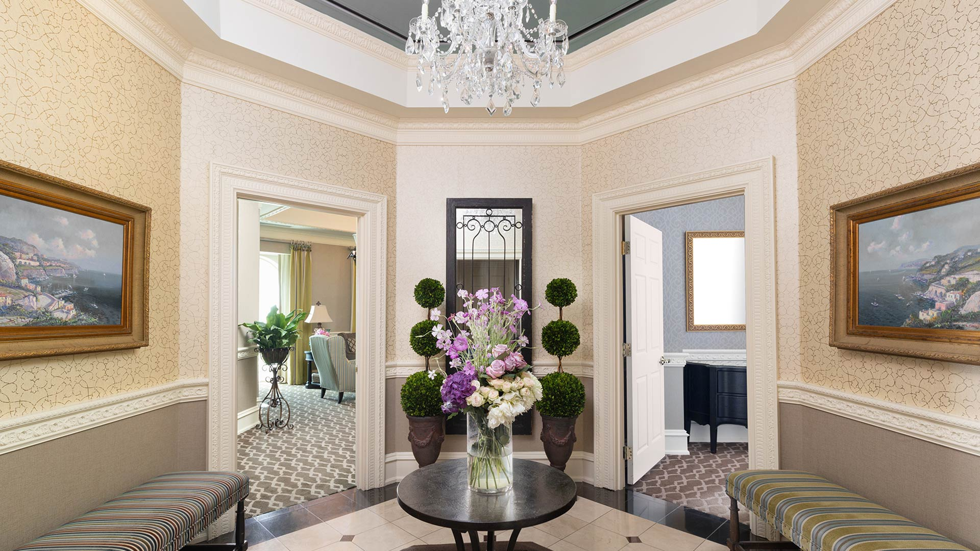 interior shot of The Chateau's presidential suite foyer. There is a round table in the center with flowers. on either side is a door leading to another room.