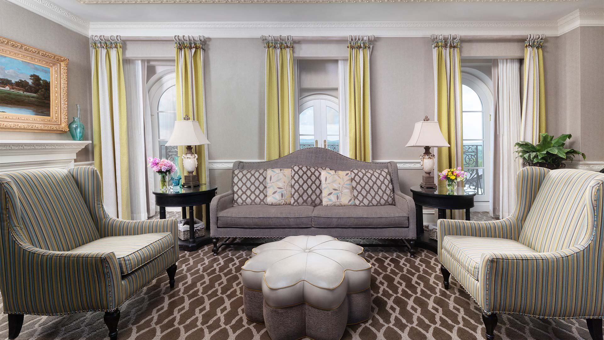 interior shot of the sitting room. There is a gray couch with two beige armchairs on either side. In the center is a floral shaped table.