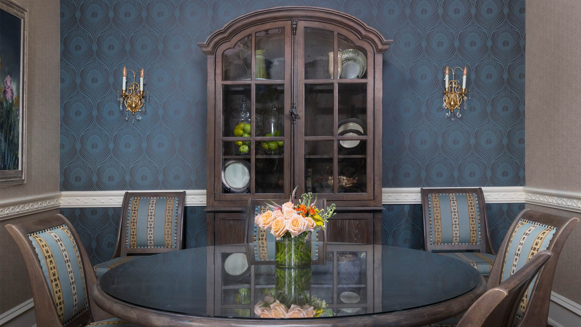 interior shot of the dining room. There is a large round table with five chairs placed around it. There is a cabinet with dish wear in it behind the table.
