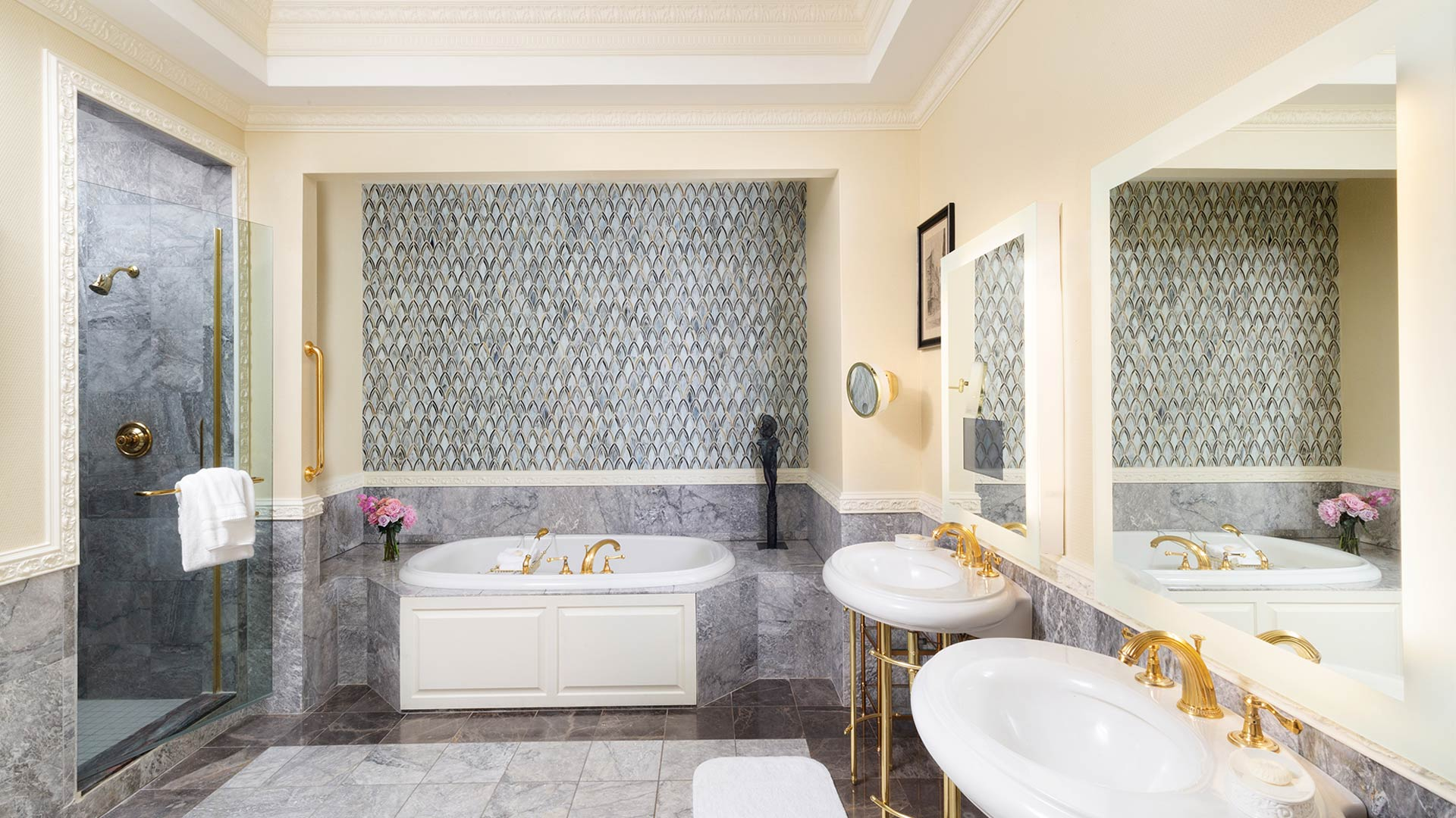 interior shot of the bathroom. There are two stand alone sinks with their own mirrors above them. There is a large walk-in shower and whirlpool bathtub.
