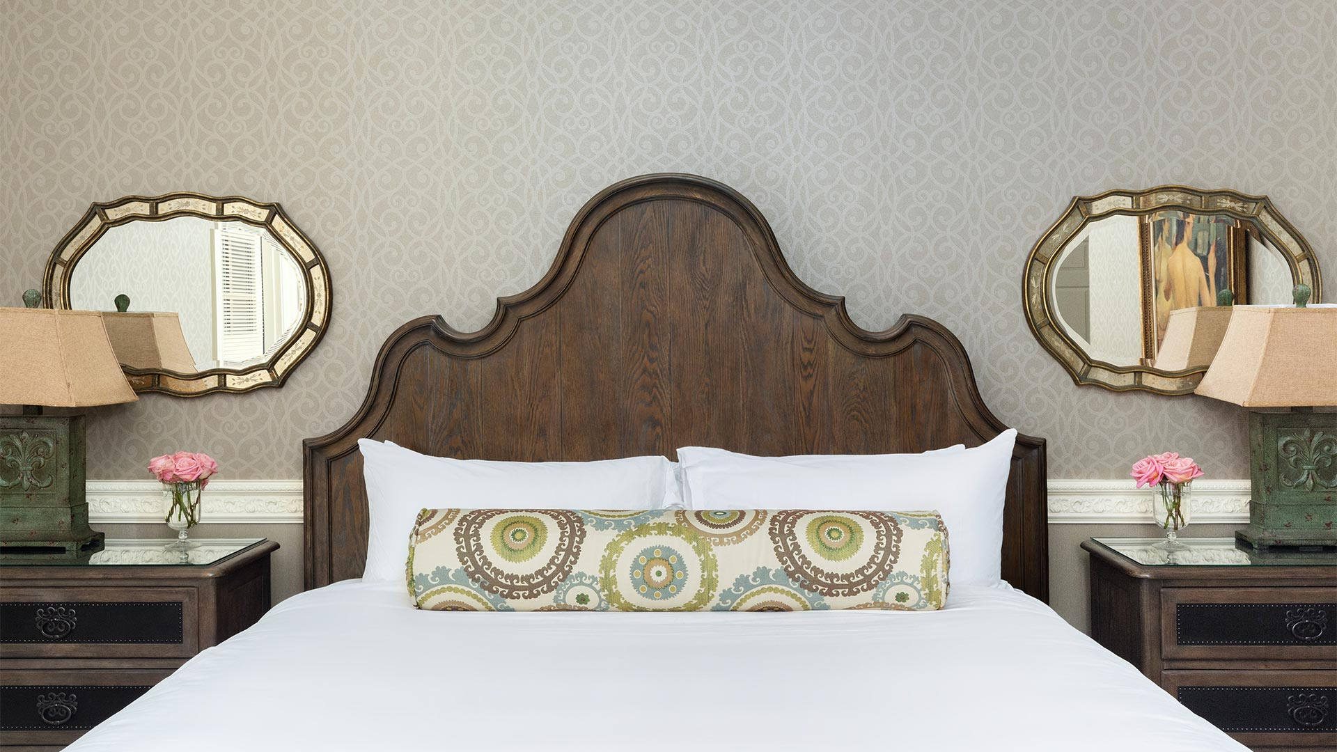 detail shot of the bed in the second room. There is a wooden headboard with a green patterned pillow. There are bed side tables on either side of the bed.