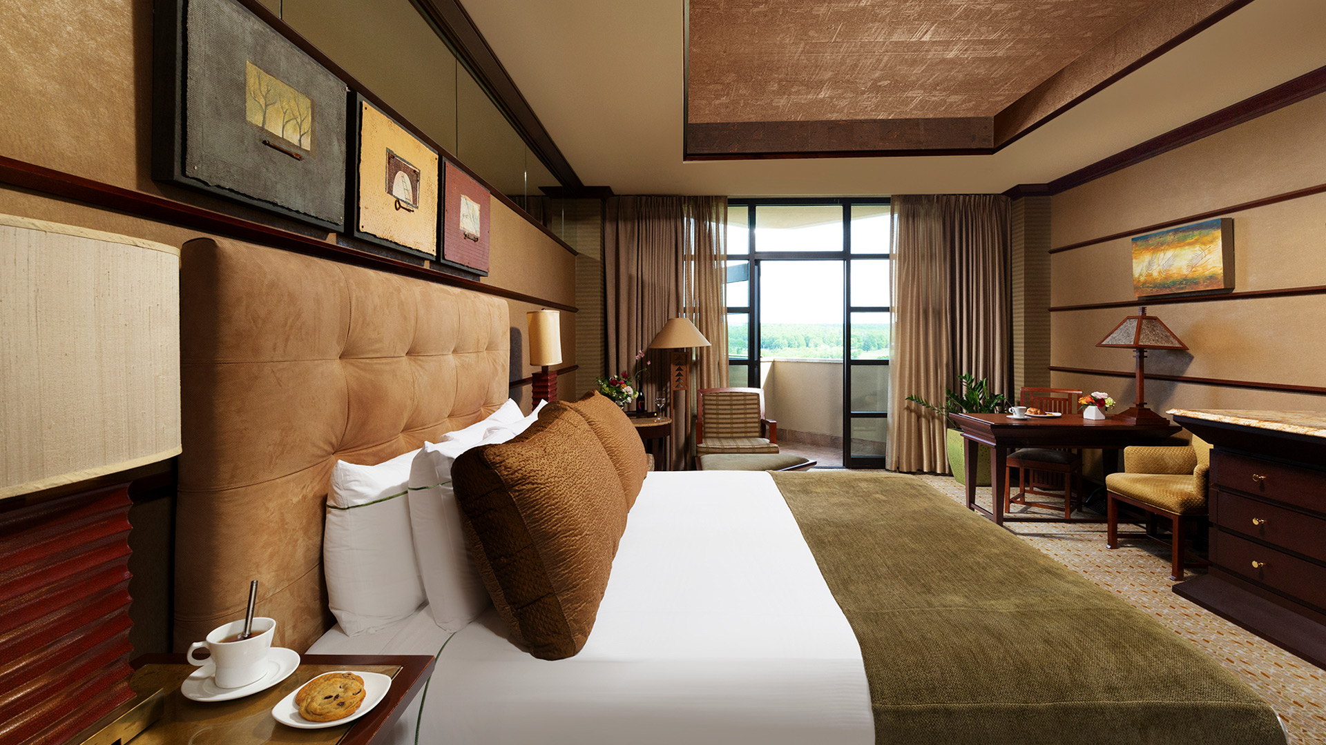 an interior shot of Falling Rock's balcony king room. There is a bed with a plush headboard and white, green and brown bedding. There is a sitting area with a table and dresser across from the bed. There is a door that leads to a balcony overlooking the resort grounds.