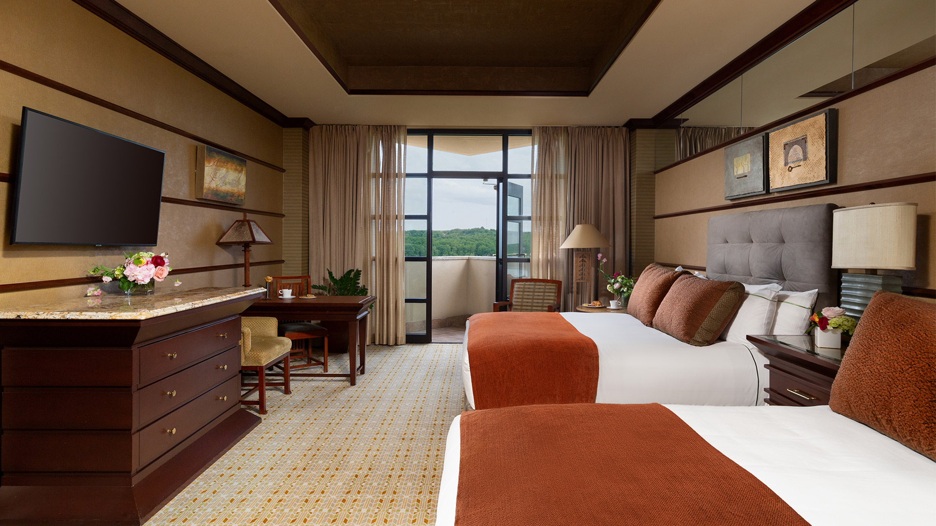 interior shot of Falling Rock's balcony double room. There are two king beds with plush headboards and white, burnt orange and brown bedding. There is a sitting area and a dresser with a flatscreen TV mounted above it. There are doors that lead to a balcony overlooking the resort grounds.