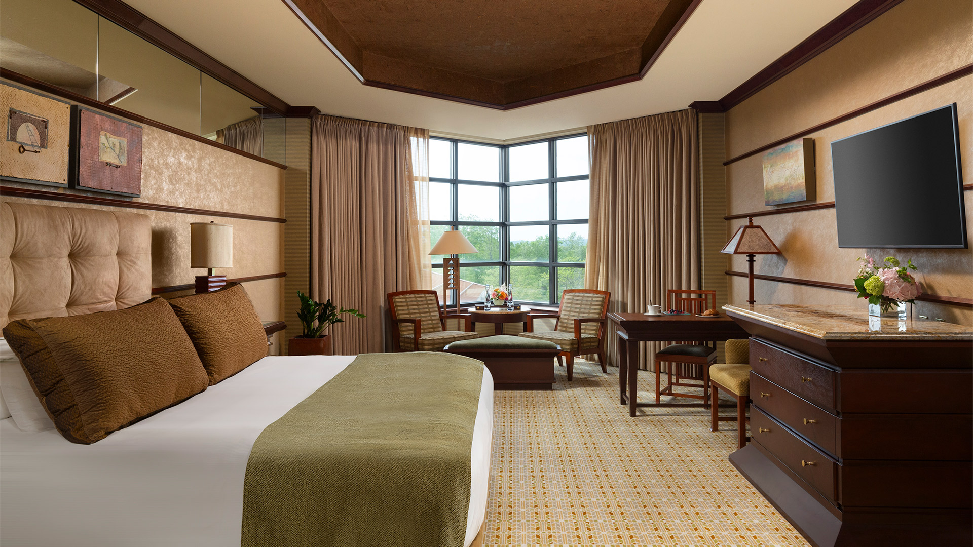 an interior shot of Falling Rock's luxury king room. There is a bed with a plush headboard and white, green and brown bedding. There is a sitting area with a table and dresser across from the bed. There are windows overlooking the resort grounds.