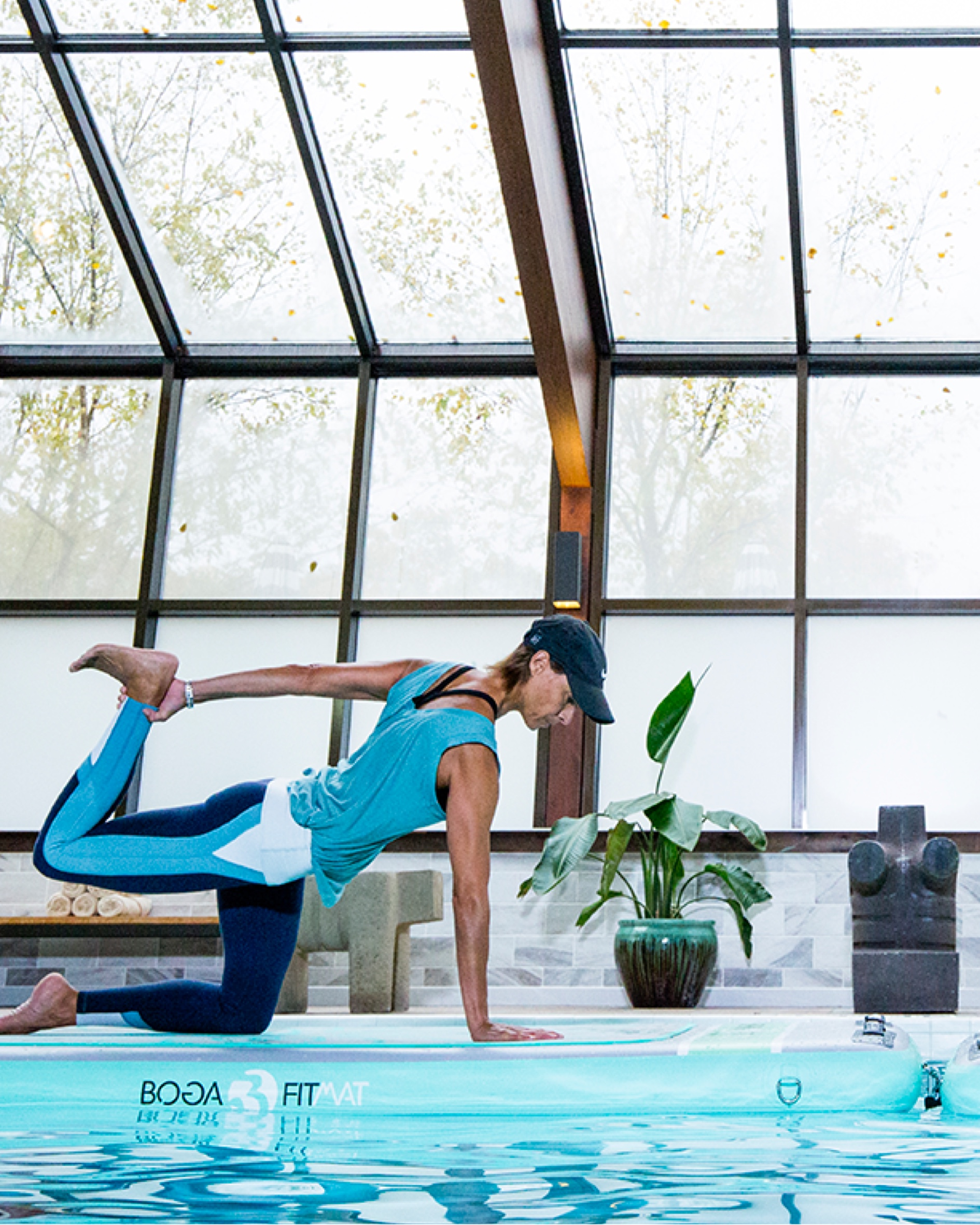 a woman doing yoga by the edge of a pool
