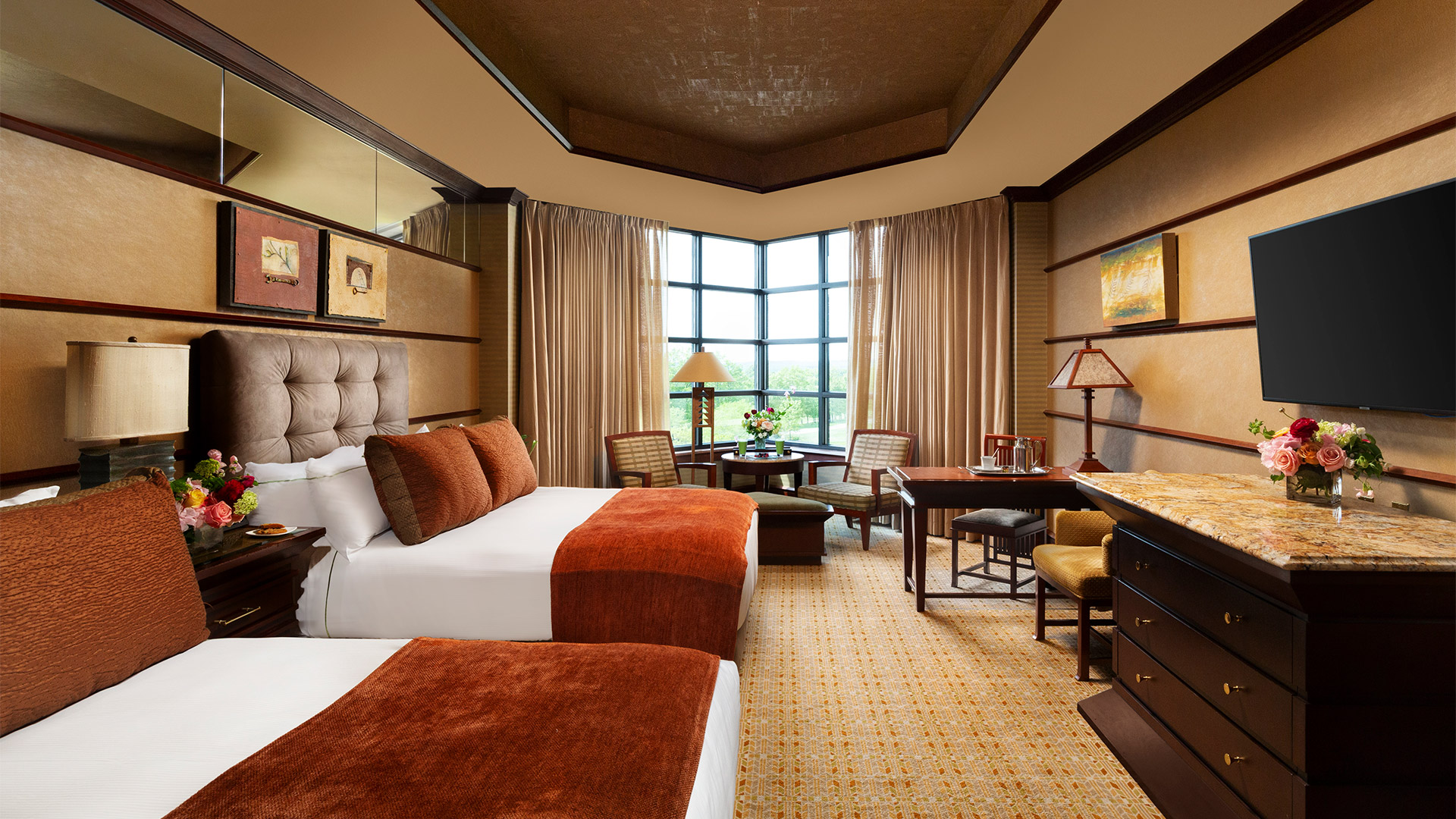 interior shot of Falling Rock's luxury double room. There are two queen size beds on the left side of the room. They have plush headboards and are decorated with white and burnt orange bedding. On the right side of the room is a dining area and a dresser with a flat screen TV mounted above it. There are windows overlooking the resort grounds with a sitting area.