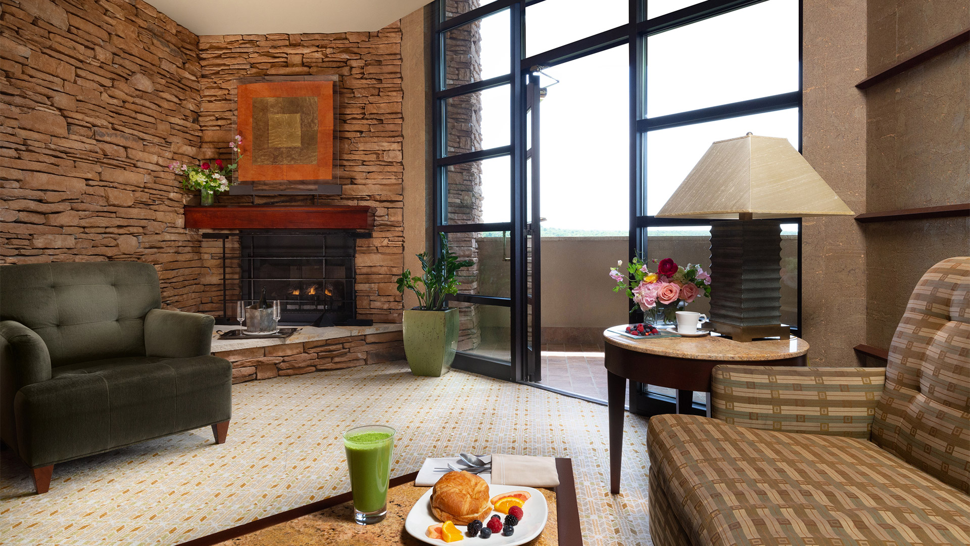 interior shot of Falling Rock's double suite living area. There is a couch and an arm chair around a coffee table with breakfast on it. There is a fireplace in the background and a door leading out onto a balcony