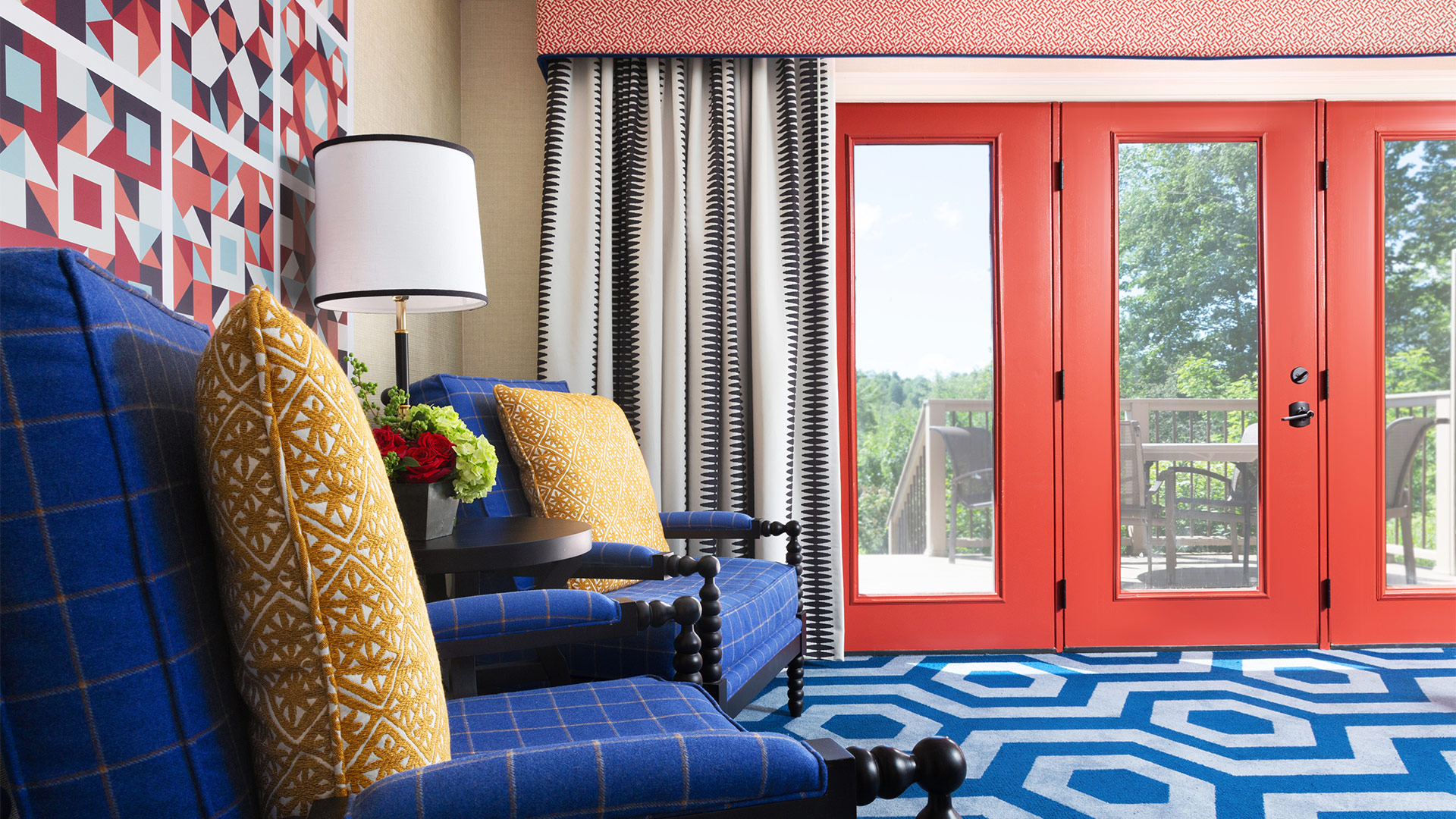 interior shot of a Washington townhome sitting area. There is a blue geometric rug, two blue chairs with yellow pillows. The room has red accents along the door and in some artwork behind the chairs.