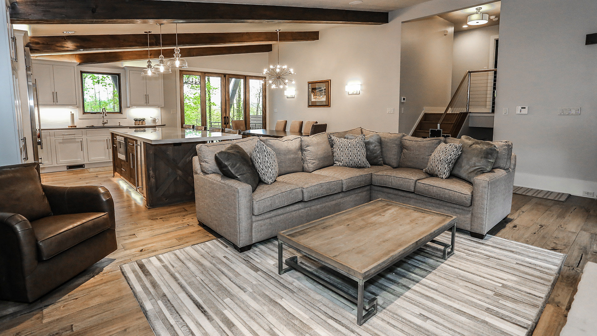 interior shot of greystone's living area. The colors in the room are a neutral gray tone. There is a plush couch surrounding a wooden coffee table. It is an open floor plan with exposed wooden beams on the ceiling.