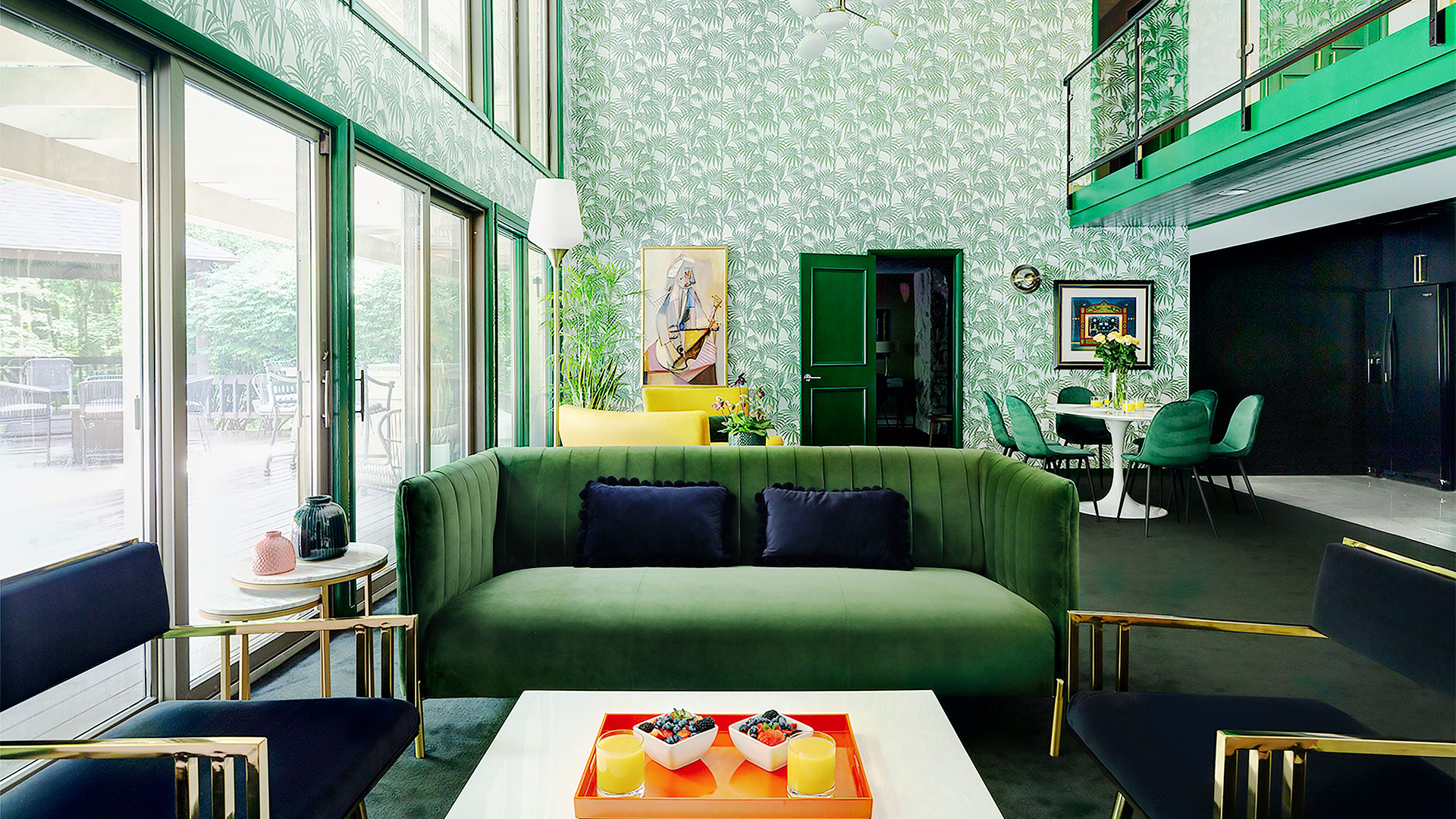 an interior shot of grouse glen's living area. The space has a stunning emerald green theme. The couch is velvet and there is patterned wallpaper in the background. Art dots the room bringing in accents of orange, red and yellow