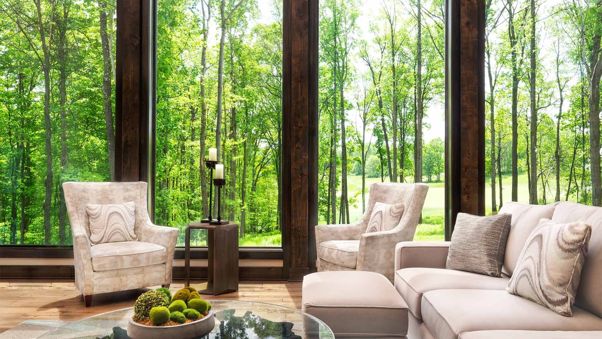 interior shot of the dogwood sitting area. There are two cream colored chairs and a matching couch around a coffee table. There are floor to ceiling windows give a view of the forest outside