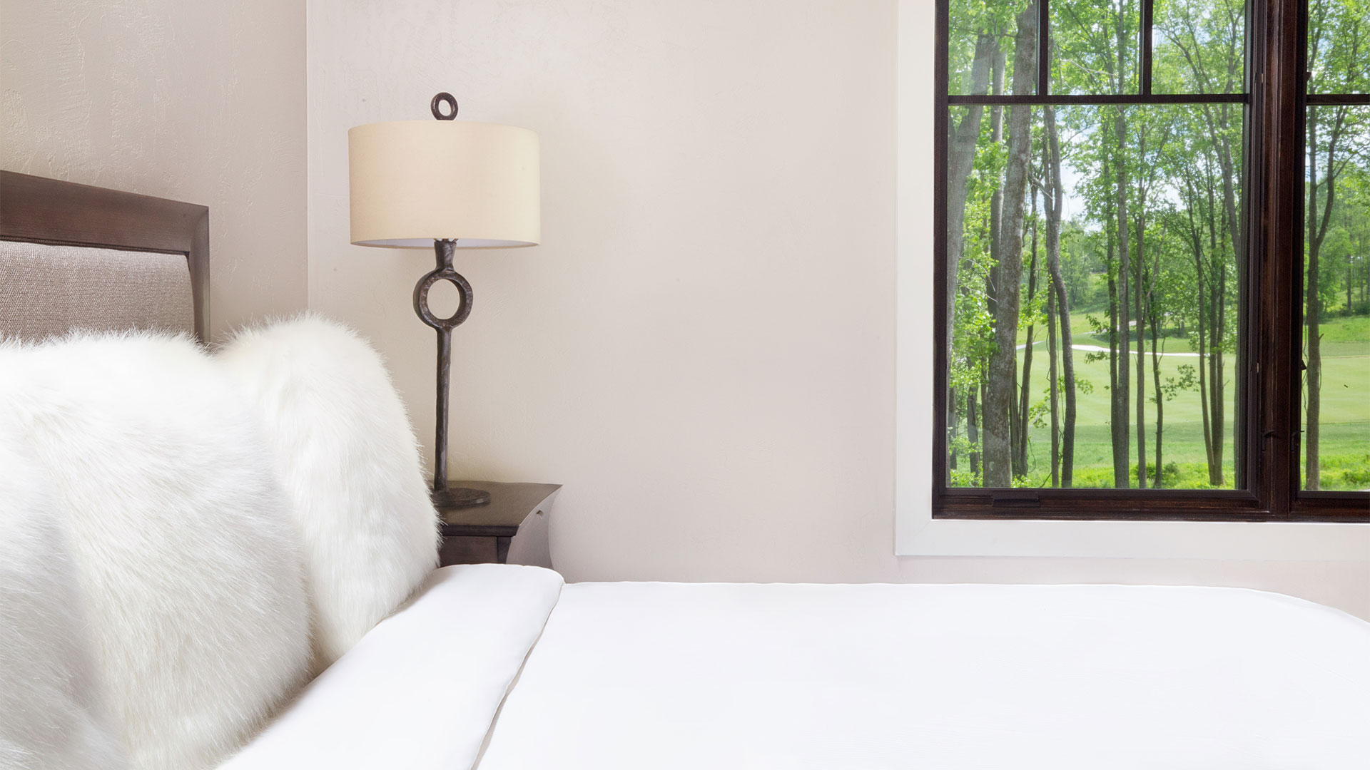 detail shot of a dogwood bedroom. There is a elegant bed with all white linens and a bedside table with a lamp