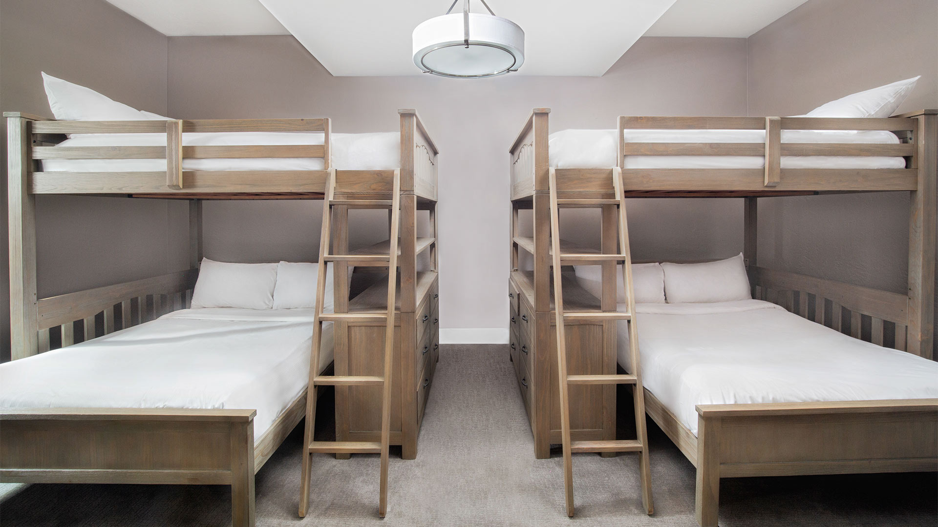 interior shot of a dogwood bedroom with two bunk beds on either side of the room. Each bed has all white linens