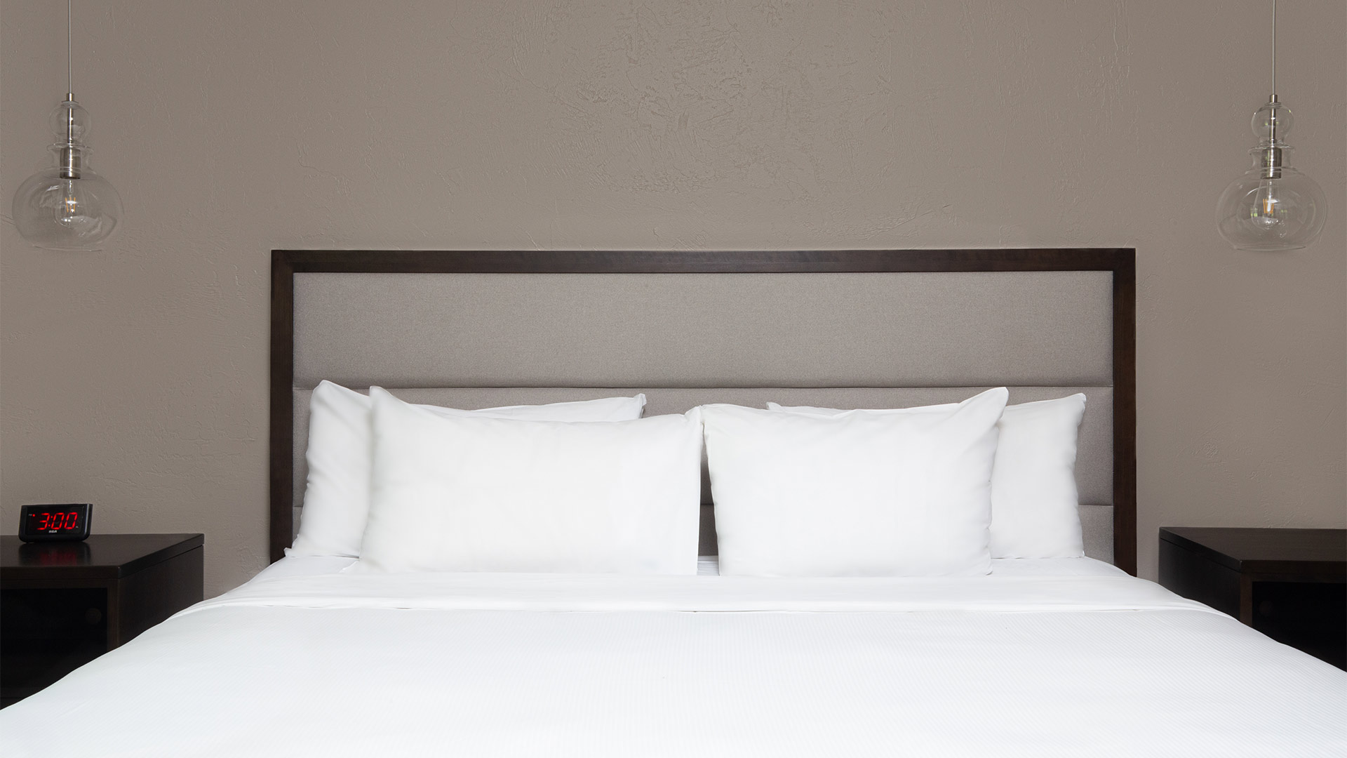 detail shot of a bed with all white linens and bed side tables on either side of the bed
