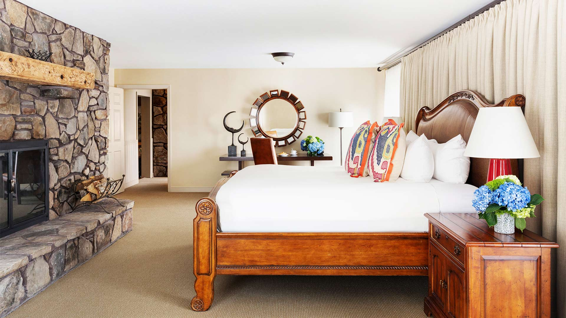 interior shot of a bedroom with a king bed with white linen and colorful throw pillows. There is a stone fireplace across from the bed. There is a vanity on the other side of the room.
