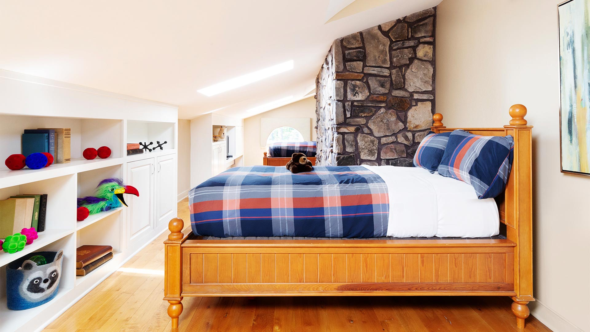 interior shot of a children's bedroom. There is a bed with plaid bedding and a shelving unit across from the bed with toys lining it.