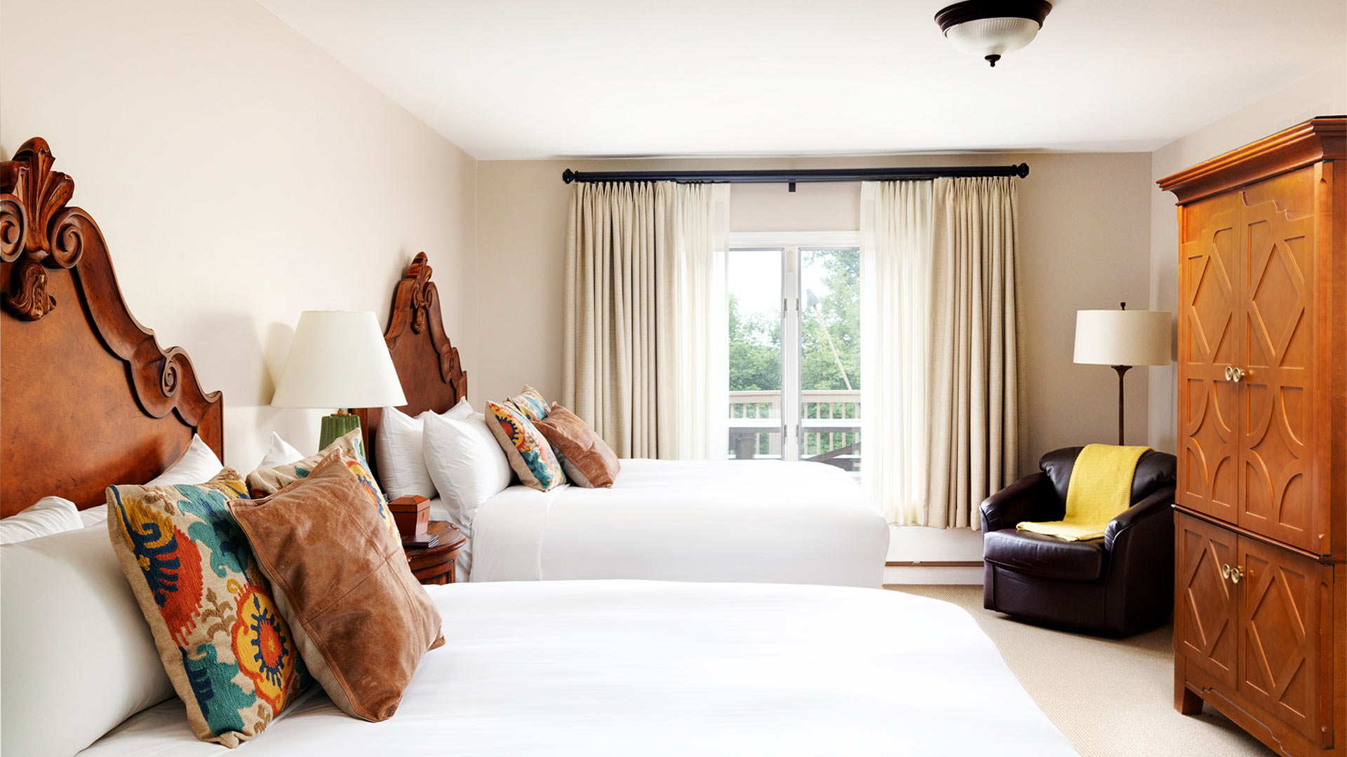 a bedroom with two queen beds. Both beds have white bedding and colorful throw pillows and intricate wooden headboards. There is a armoir and small sitting area on the other side of the room