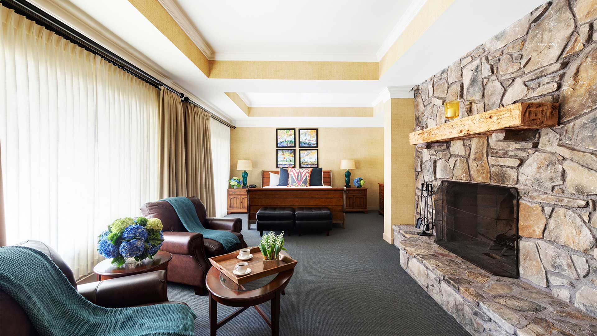 interior shot of a bedroom. There are brown leather chairs across from a large stone fireplace. There is a bed on the other side of the room with tables on either side of it.