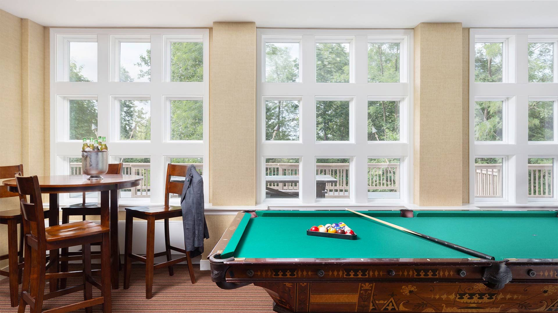 interior shot of a game room with a pool table and a table.
