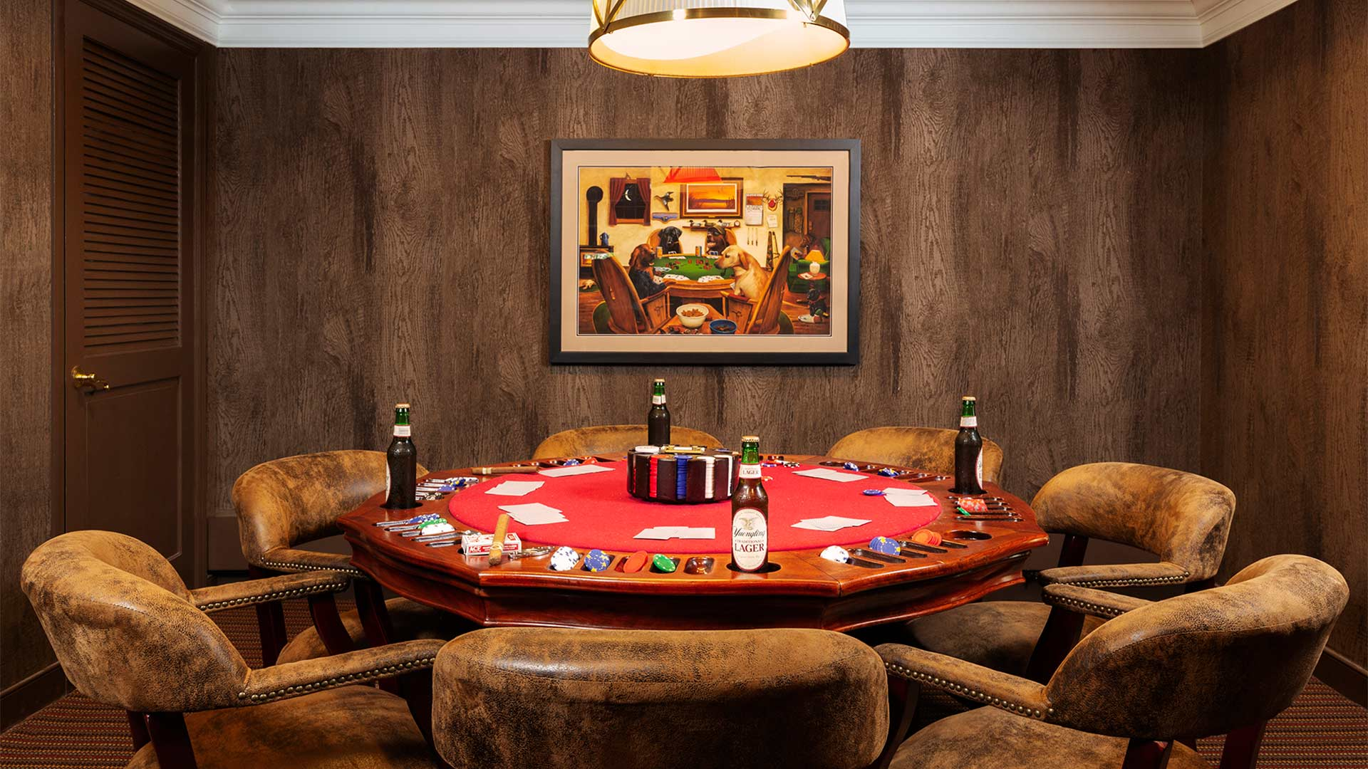 interior shot of a card room. The room has dark wood panels on the walls and the poker table is round and red. There are several plush chairs around the table