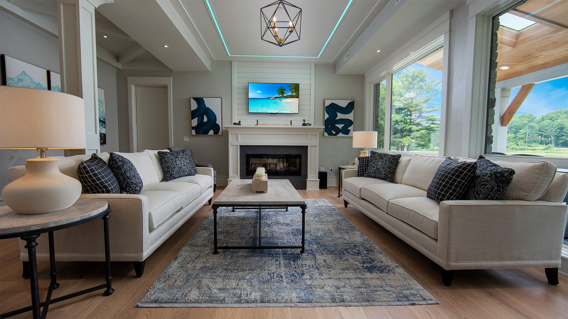 an interior shot of the living area. There are two neutral colored couches across from each other with a coffee table between them. There is a fireplace with modern art pieces on either side of the mantle.