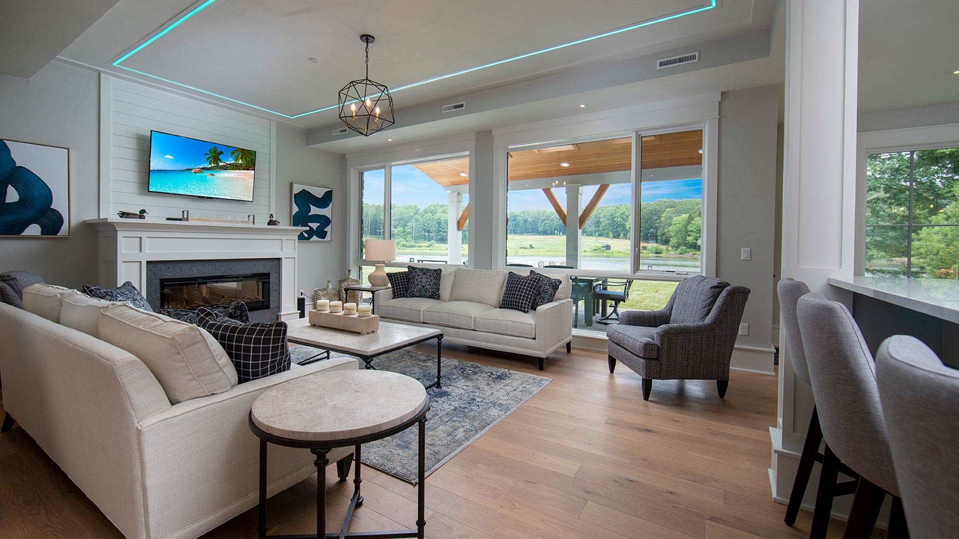 an interior shot of the living area. There are two neutral colored couches across from each other with a coffee table between them. There is a fireplace with modern art pieces on either side of the mantle. There is a sliding glass door leading out to a patio.