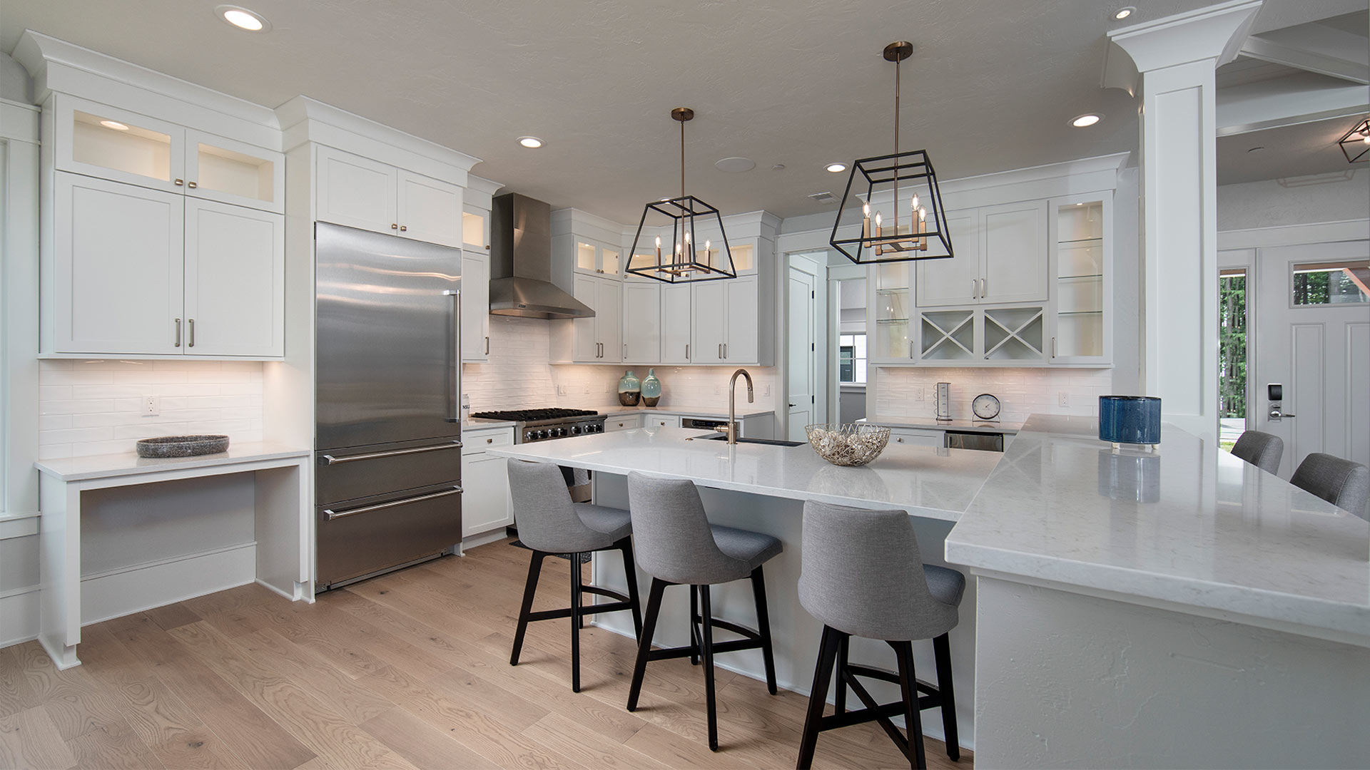 interior shot of a kitchen. The countertops and cabinets are a sleek white. There are gray chairs lining the kitchen island. There are stainless steel appliances.