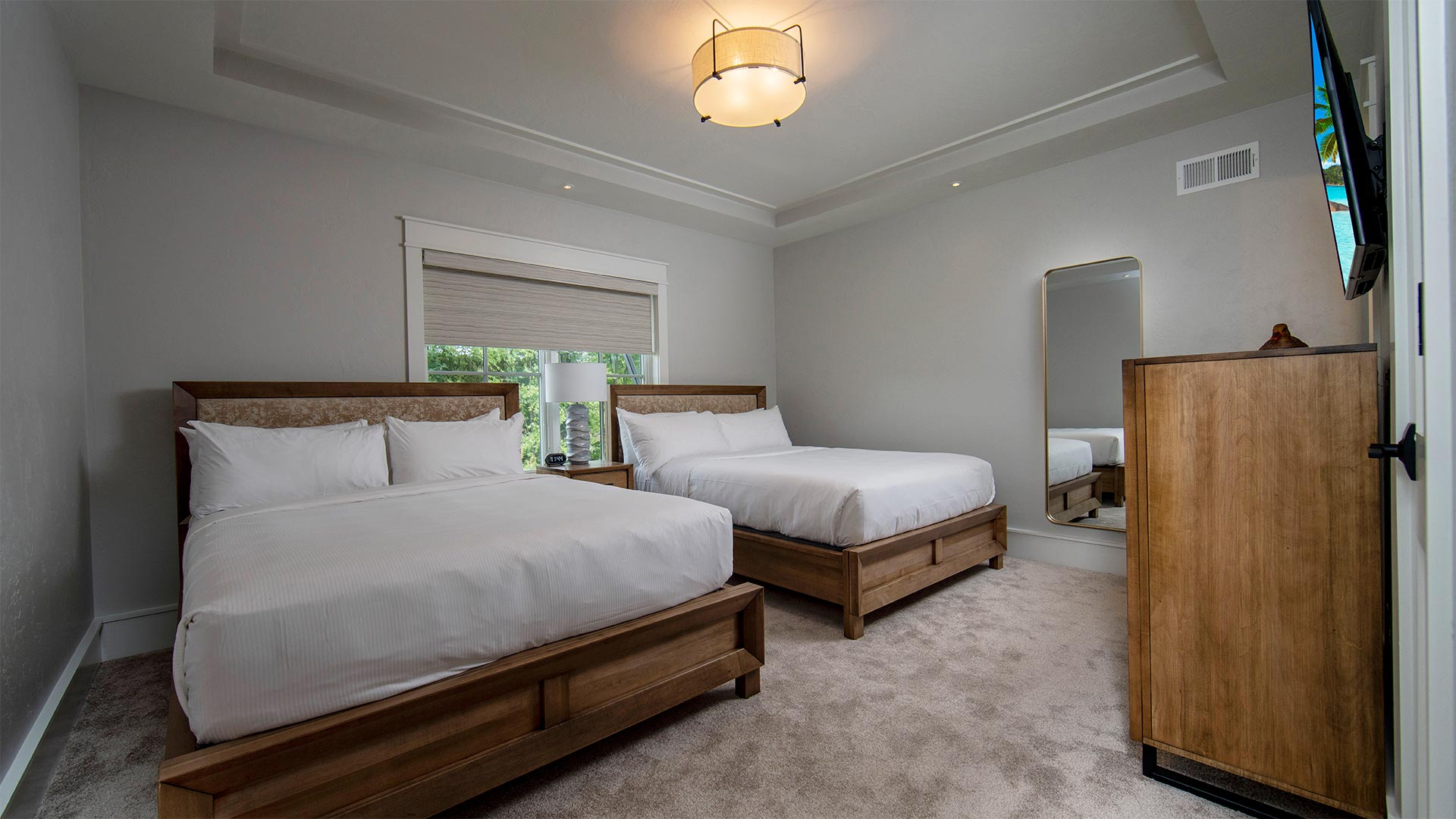 interior shot of a bedroom with two queen beds. Each bed has all white linens and wooden headboard. There is a dresser with a tv mounted overhead across from the beds