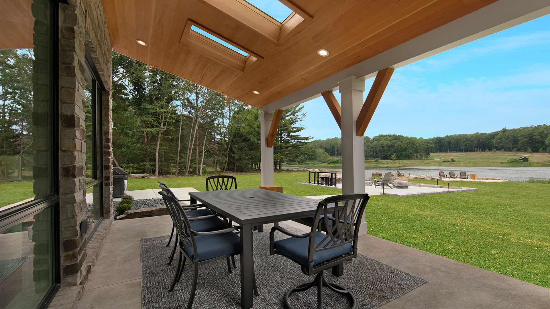 exterior shot of the patio with a table and chairs. There is a covering over the patio and a view of the lake