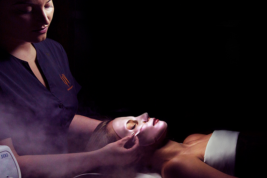 a woman getting a spa treatment. she is laying down and having a face mask being applied by a specialist.