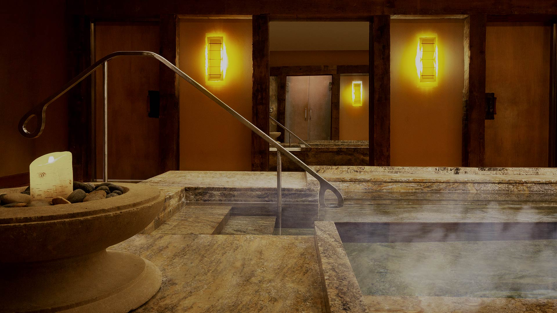 interior shot of a spa hot tub. there is soft lighting, lit candles and steam rising from the hot tub