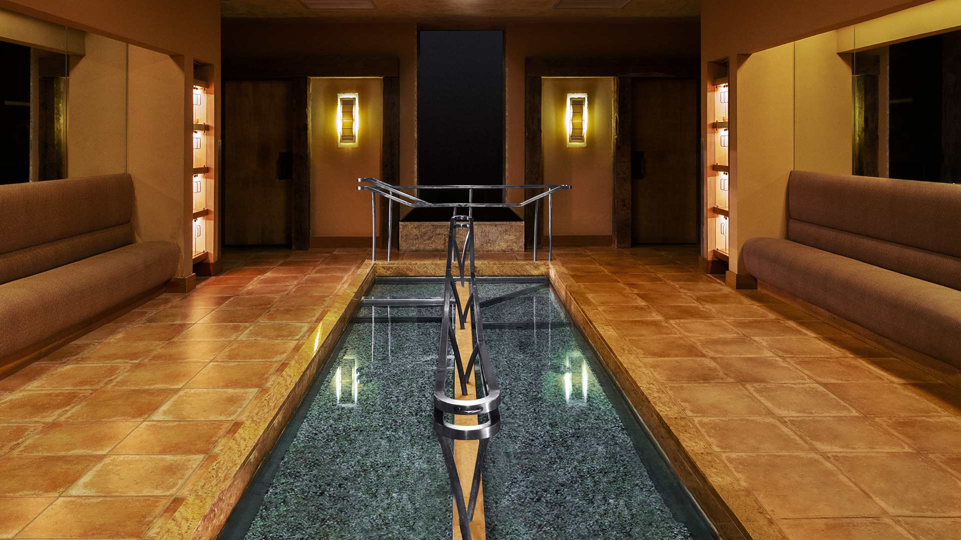 dark, warming interiors surround a thin, long dipping pool