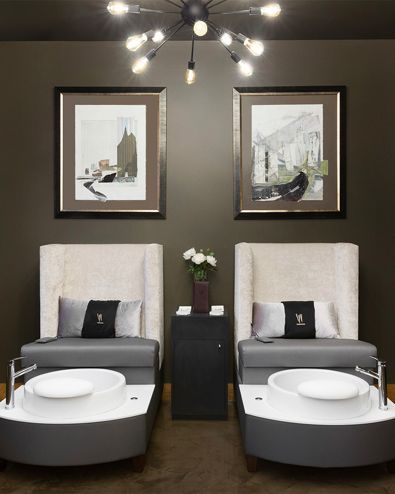 two plush chairs with a foot bath at the foot of each chair.
