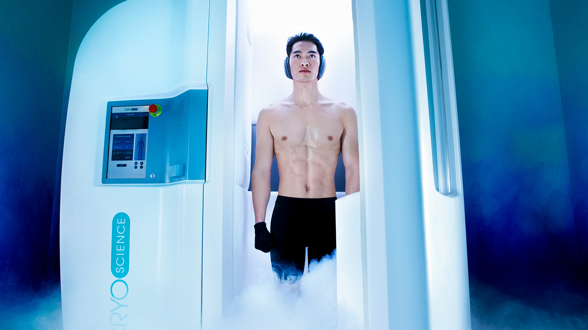 a shirtless man is walking out of a white chamber. The lighting is blue and there is steam coming out of the chamber