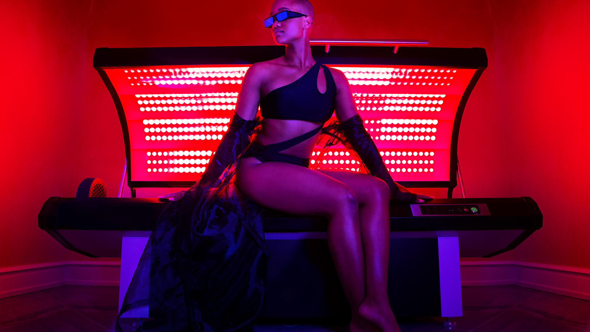 a woman dressed in a fashionable black bikini is sitting on a infrared light bed